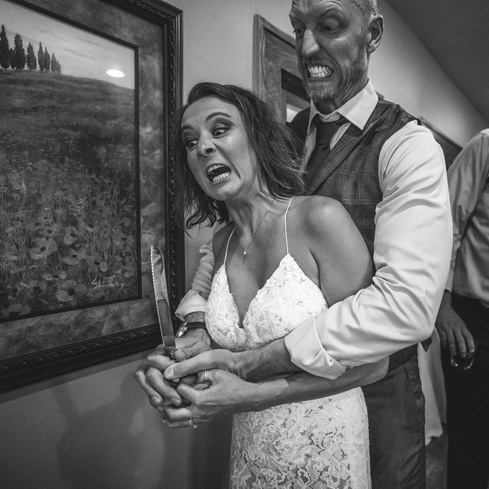 Black and white photo of a bride and groom messing around as they cut they cake, pretending they're going to use the knife to stab each other