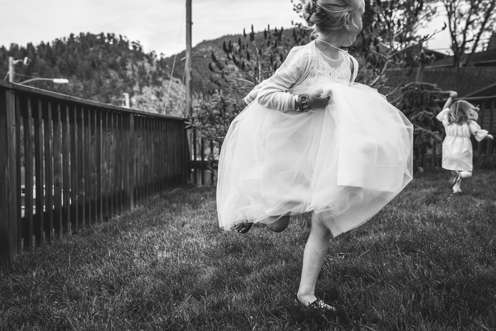 Black and white photo of a little girl in the foreground, running through the grass while wearing a white puffy dress while looking behind her at another little girl in a white dress running in the opposite direction. The mountains can be seen in the background.