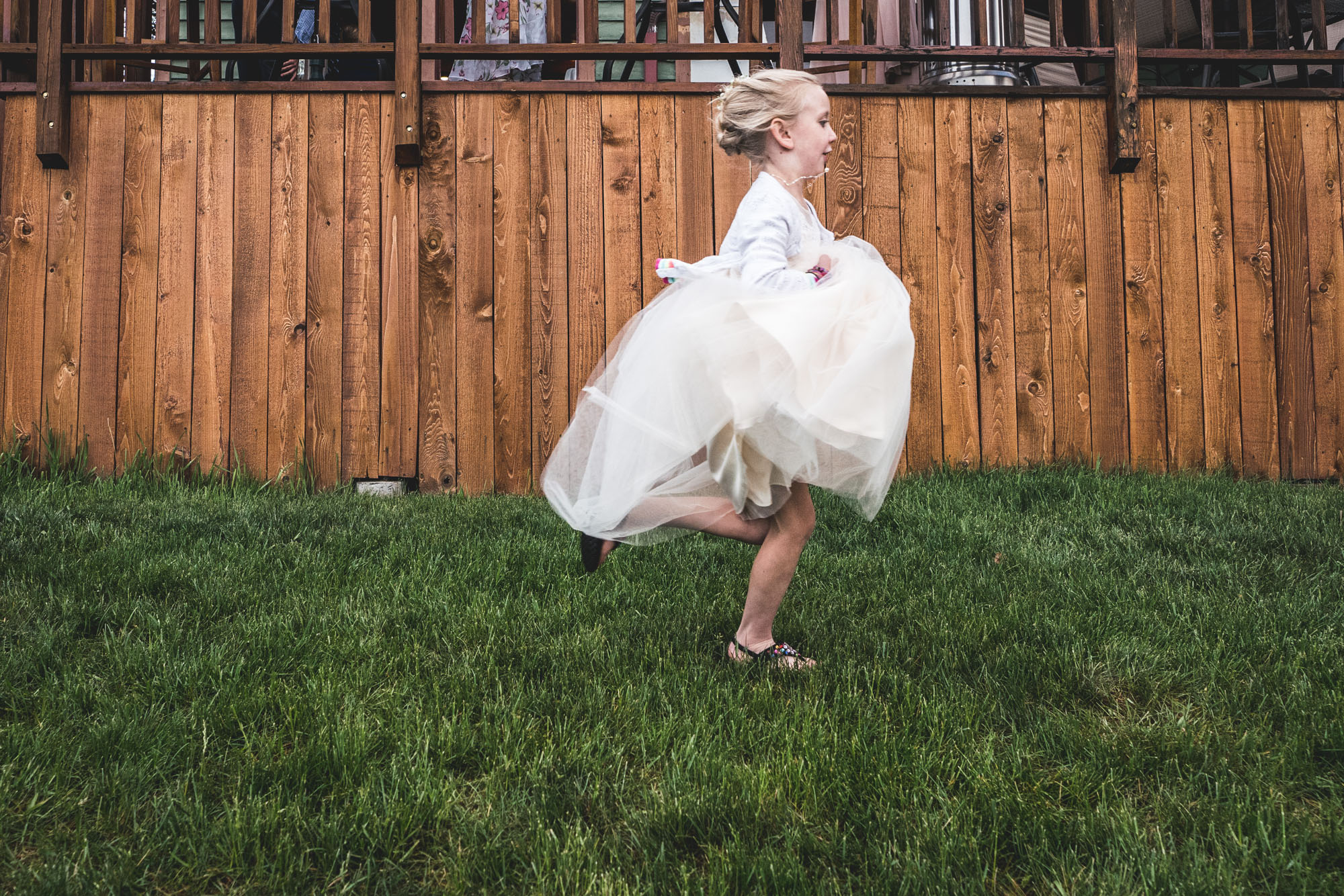 Color photo of a little girl in a white puffy dress running through the dark green grass with a wood deck as her backdrop