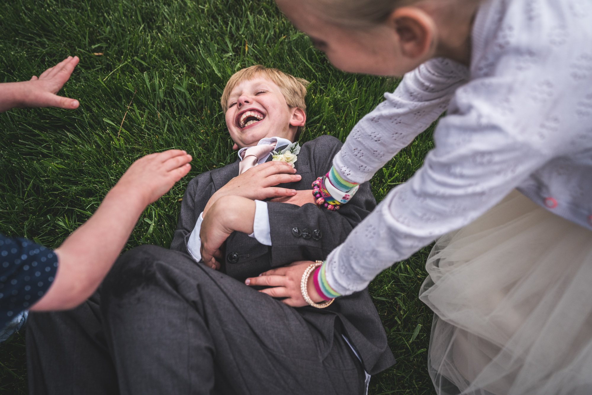 Color photo of a little boy wearing a grey suit and light pink tie lying on the grass laughing as two of his friends - one a little girl in a puffy white dress and another a little boy in a blue shirt - tickle him.