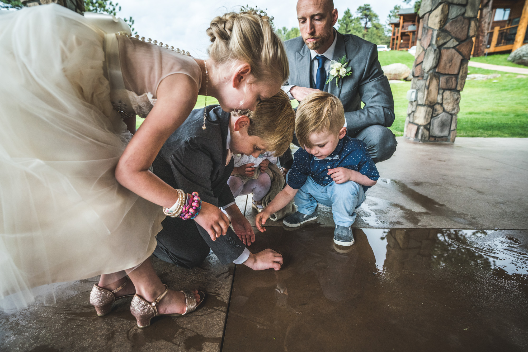 Color image taken during a wedding at the Black Canyon Inn in Estes Park, Colorado. Four kids in formal clothing bend down and look at something on the ground as the groom looks on in the background.