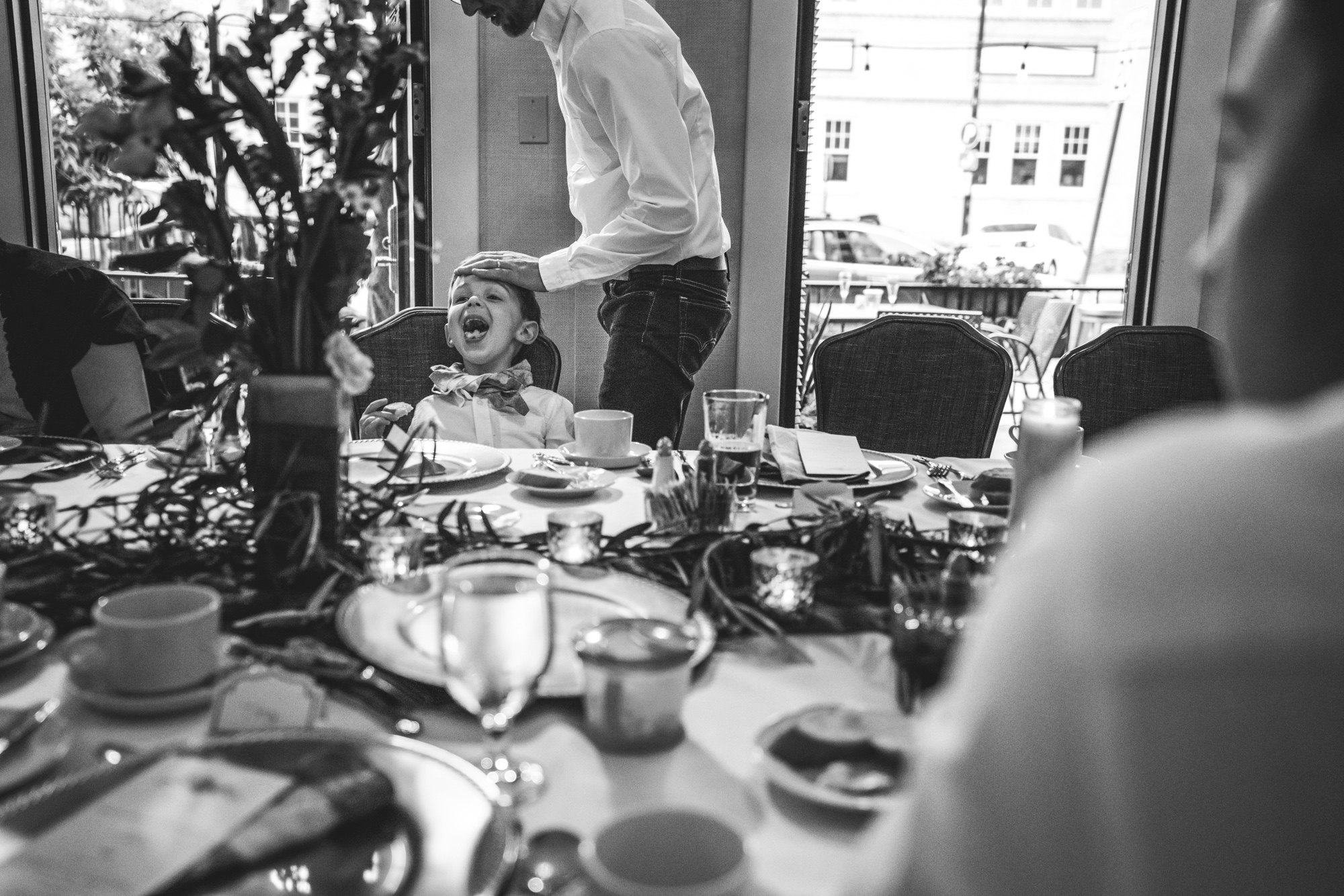 Black and white photo of a little boy at a table at a wedding reception, opening his mouth wide with it full of food as his father touches him on the head