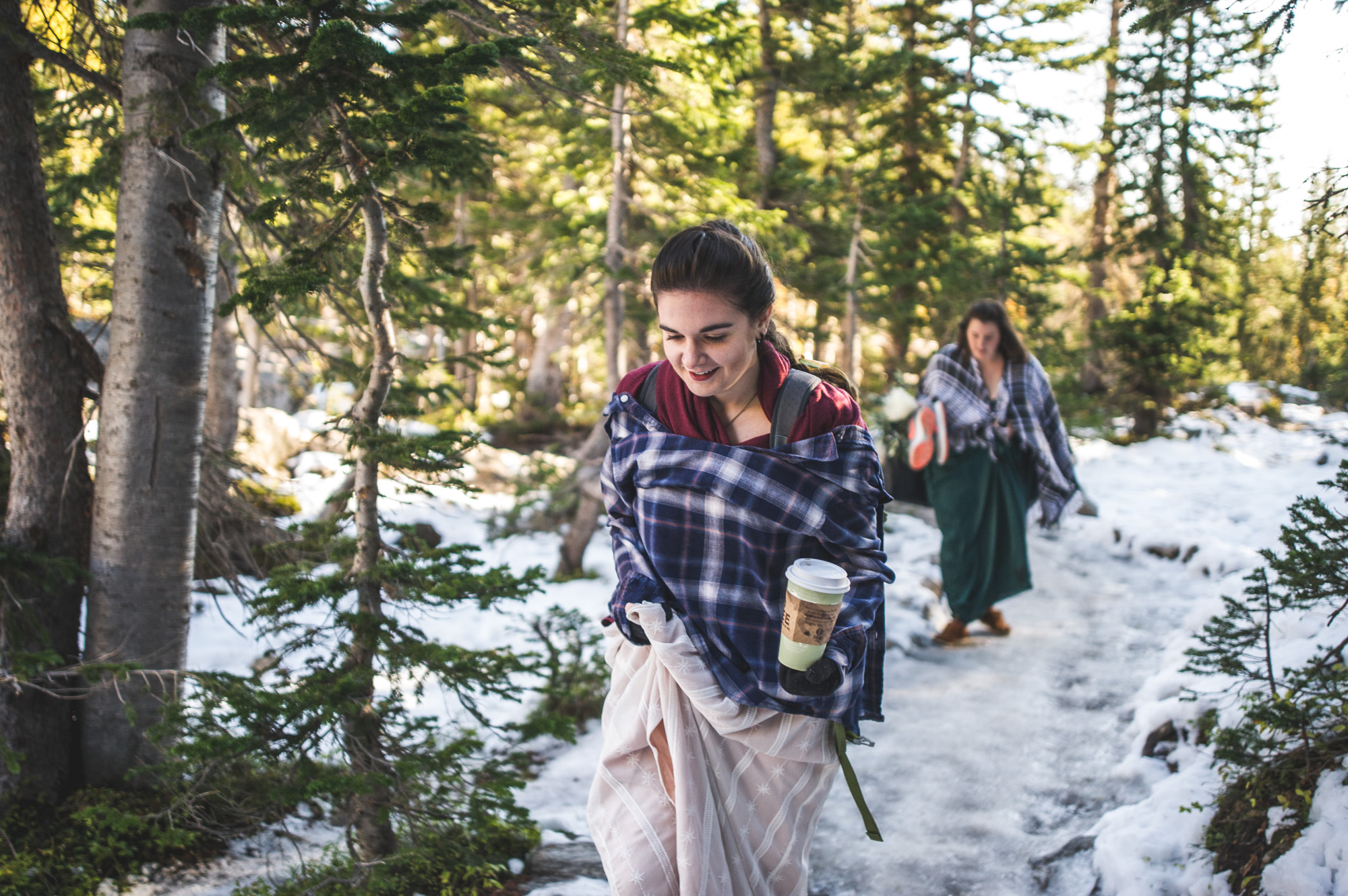 Color photo of a bride and her maid of honor walking in the Rocky Mountains with snow covered ground in their ceremony dresses