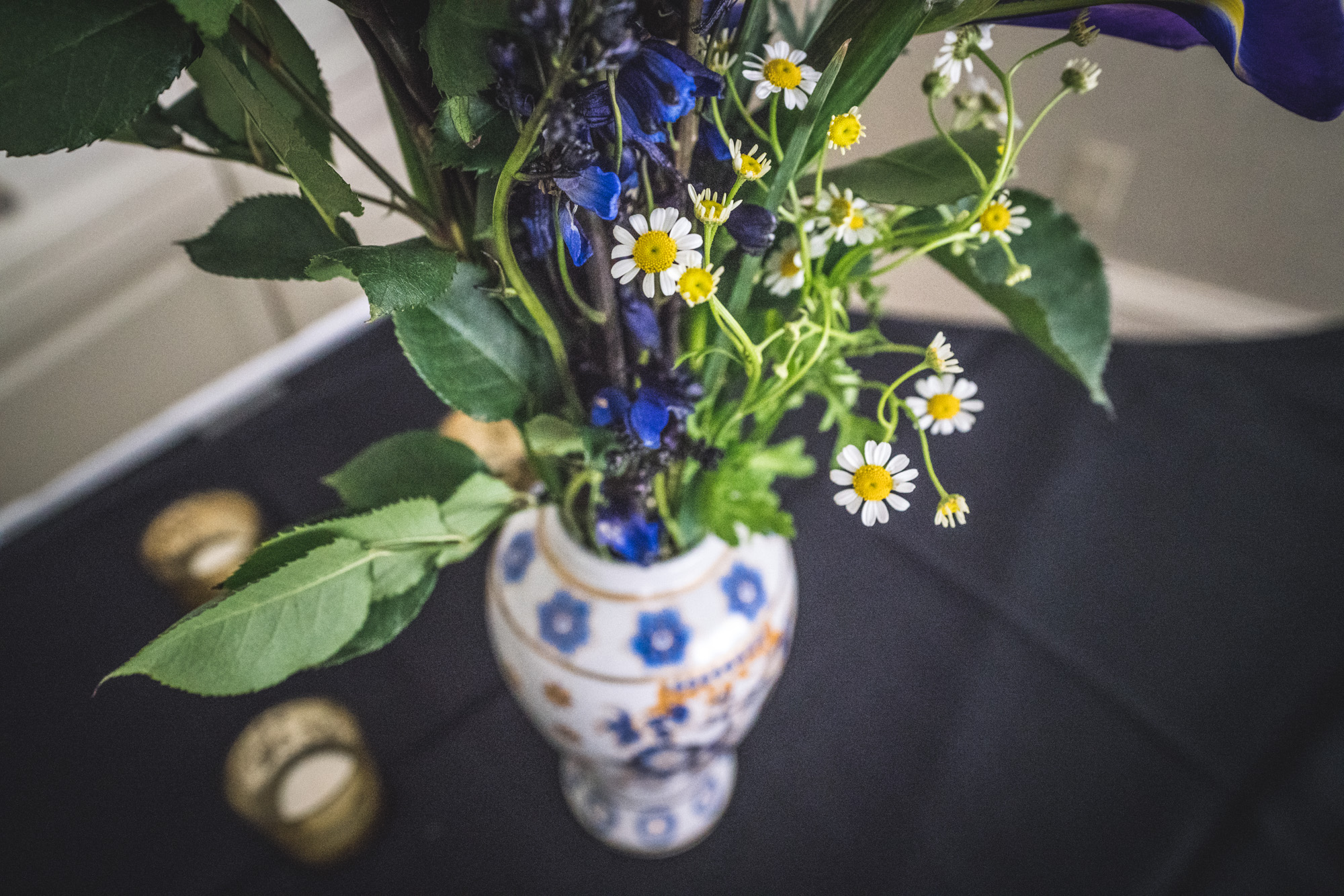 Tiny white flowers with yellow middles as well as blue irises rest in a white and blue vase on a table at a wedding reception