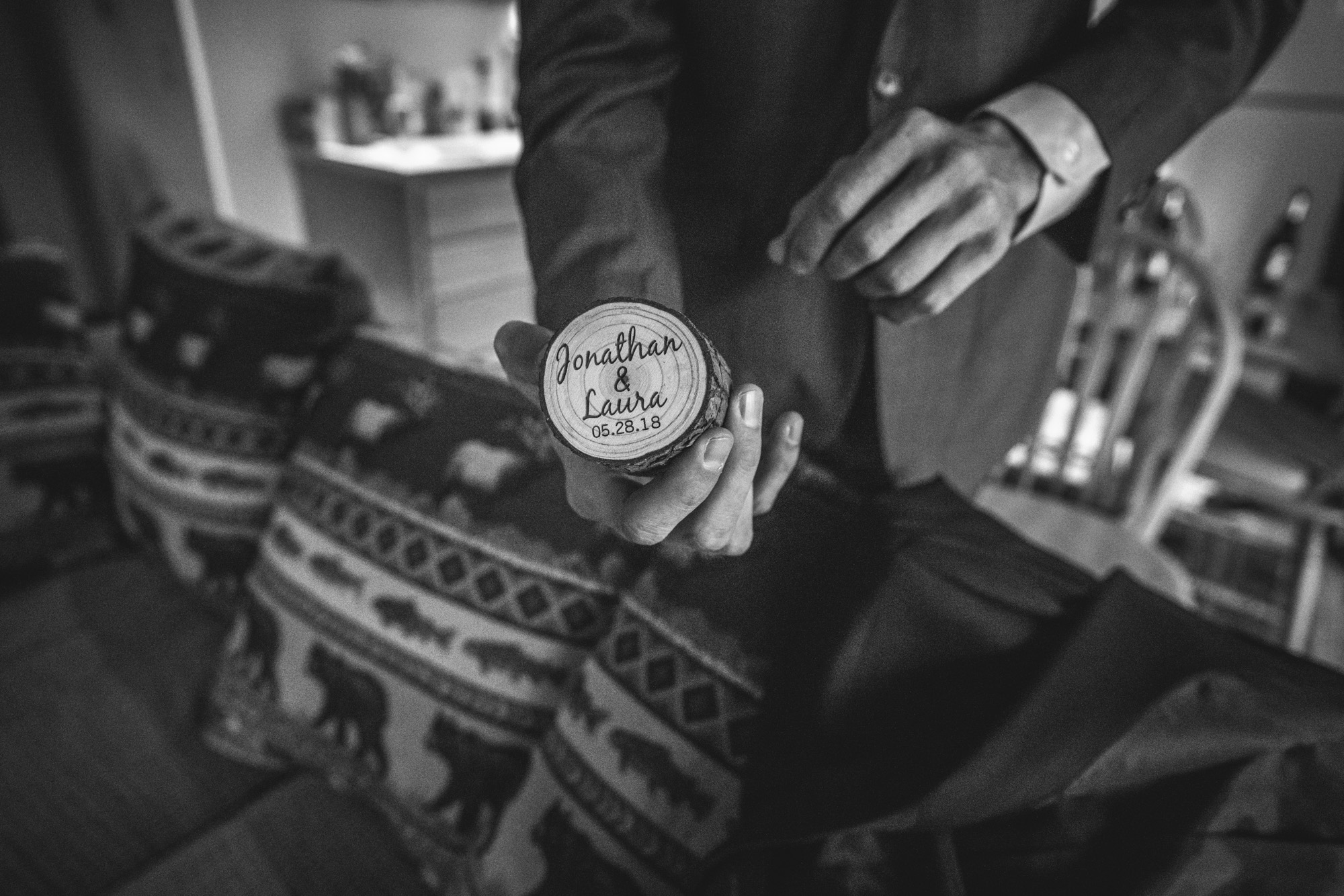 """Groom holds a small, circular wooden ring box engraved with """"Jonathan & Laura 05.28.18"""", the date of their wedding"""
