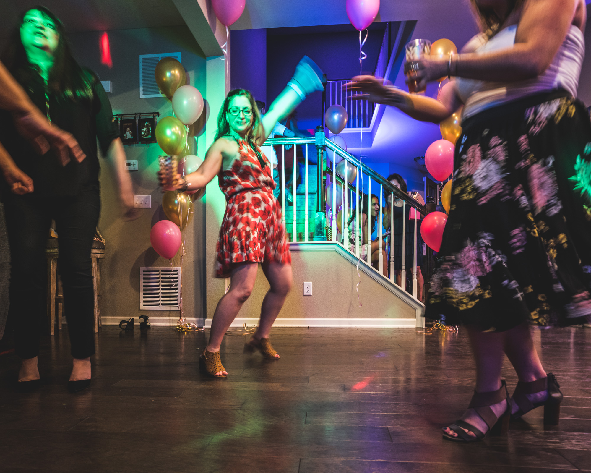 Event photograph of a woman at a house party with bright, colorful lights waving her arms around and dancing