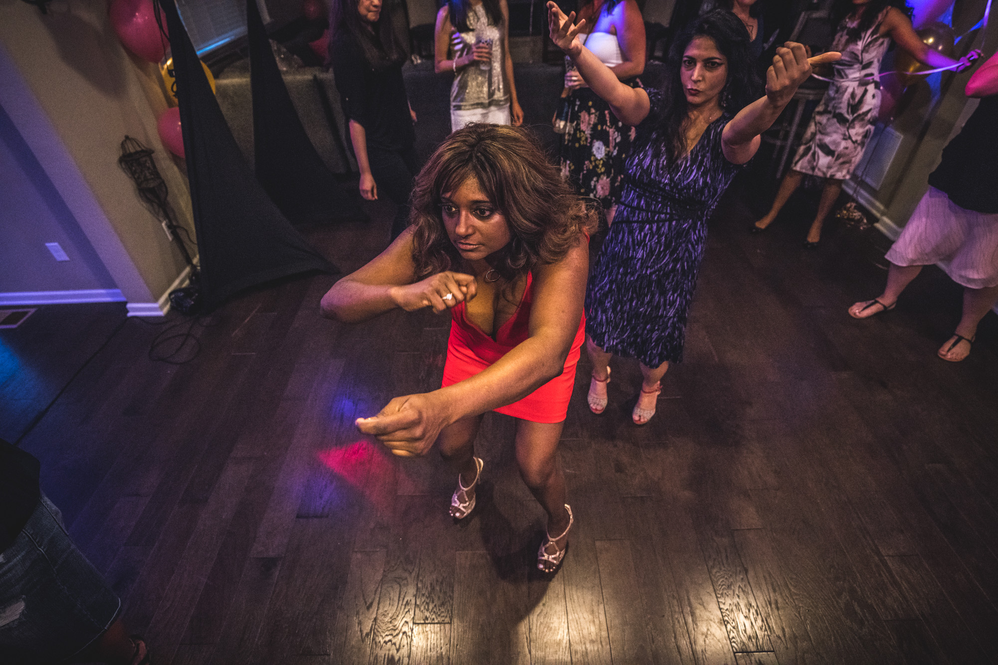 Two women in dresses dance crazily on a dance floor at a house party in Denver, Colorado