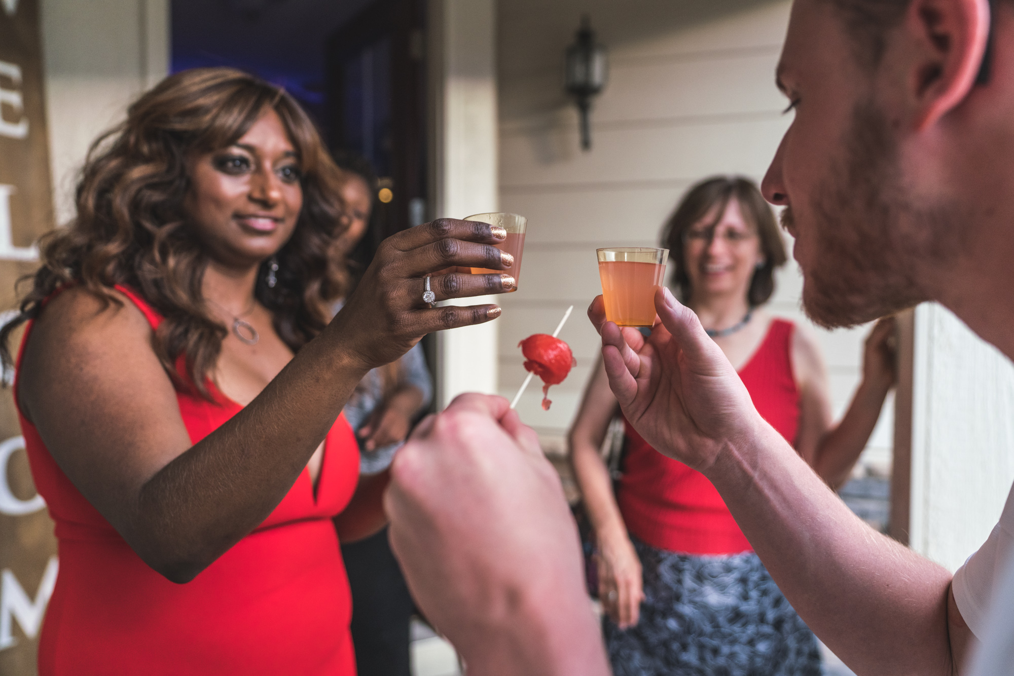 Woman in a bright red dress holds up a shot to cheers with her boyfriend