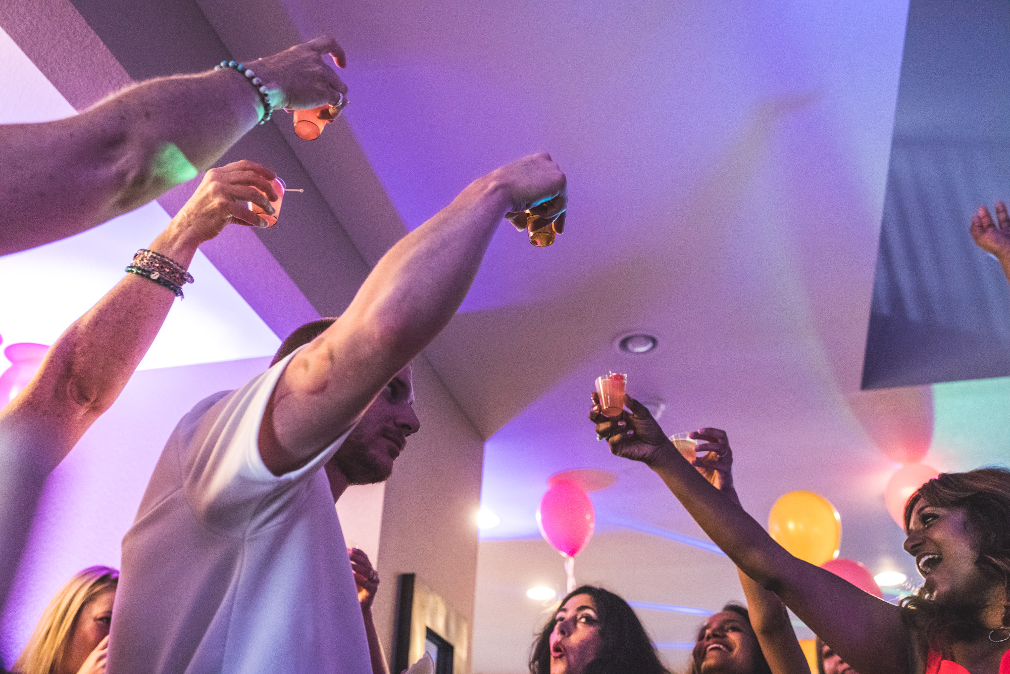A large group of friends raises shots in celebration of a birthday, with brightly colored lights and balloons decorating the scene