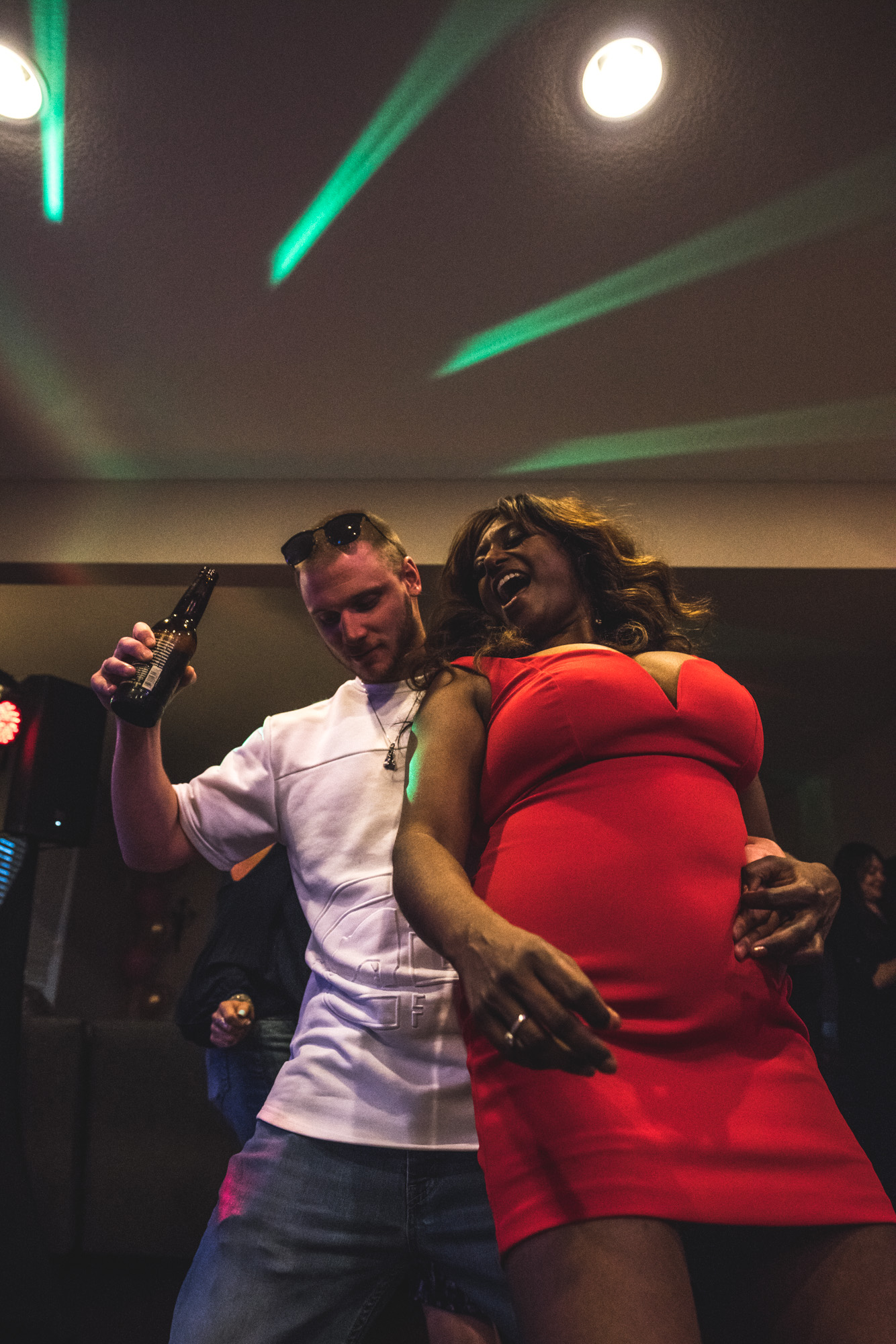 Woman in a bright red dress dances with her boyfriend at her birthday party at her home in Denver, Colorado