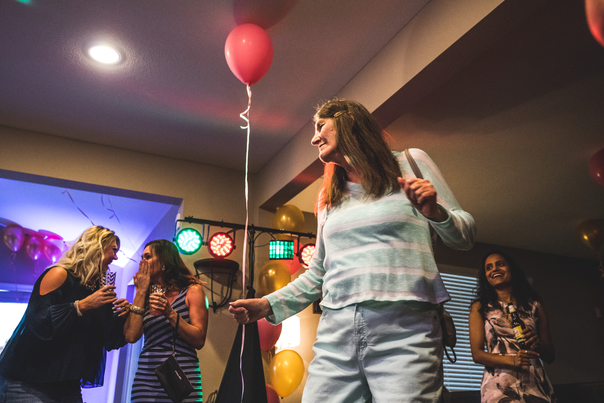 Woman dances to music at a brightly decorated house party at her friend's home in Denver, Colorado