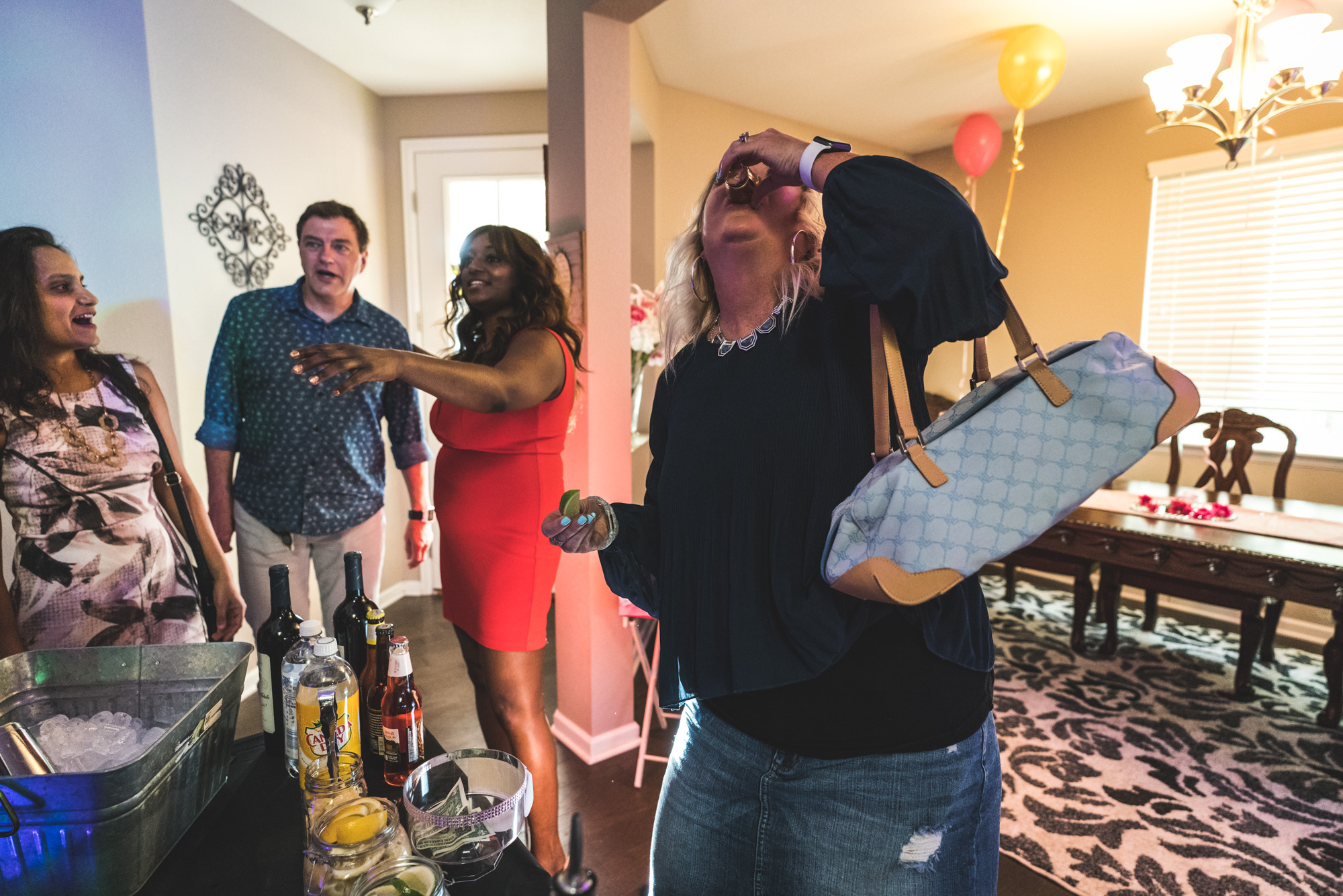 Woman holding a purse takes a tequila shot at a house party in Denver