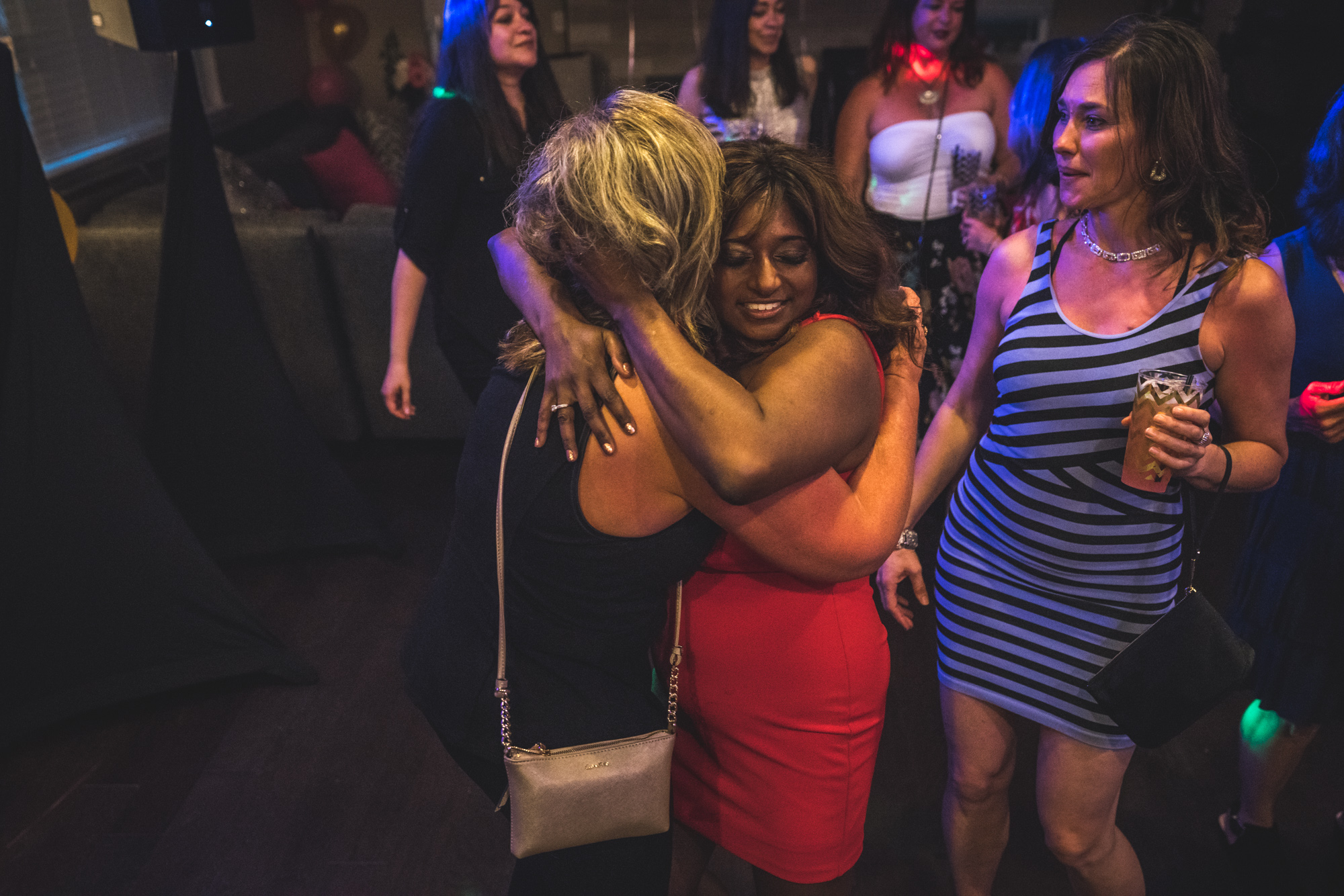 Woman in a red dress hugs woman in a black dress in the middle of a house party