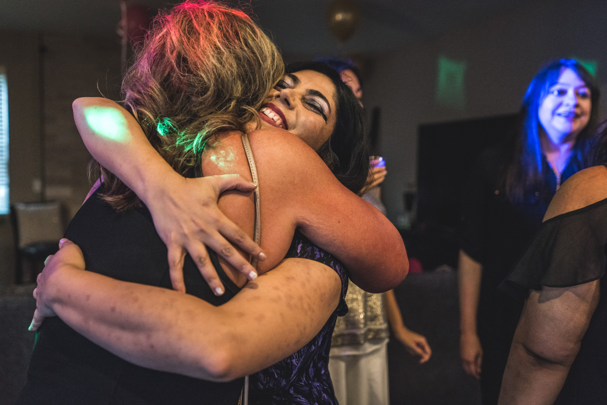 Two women embrace at a house party in Denver