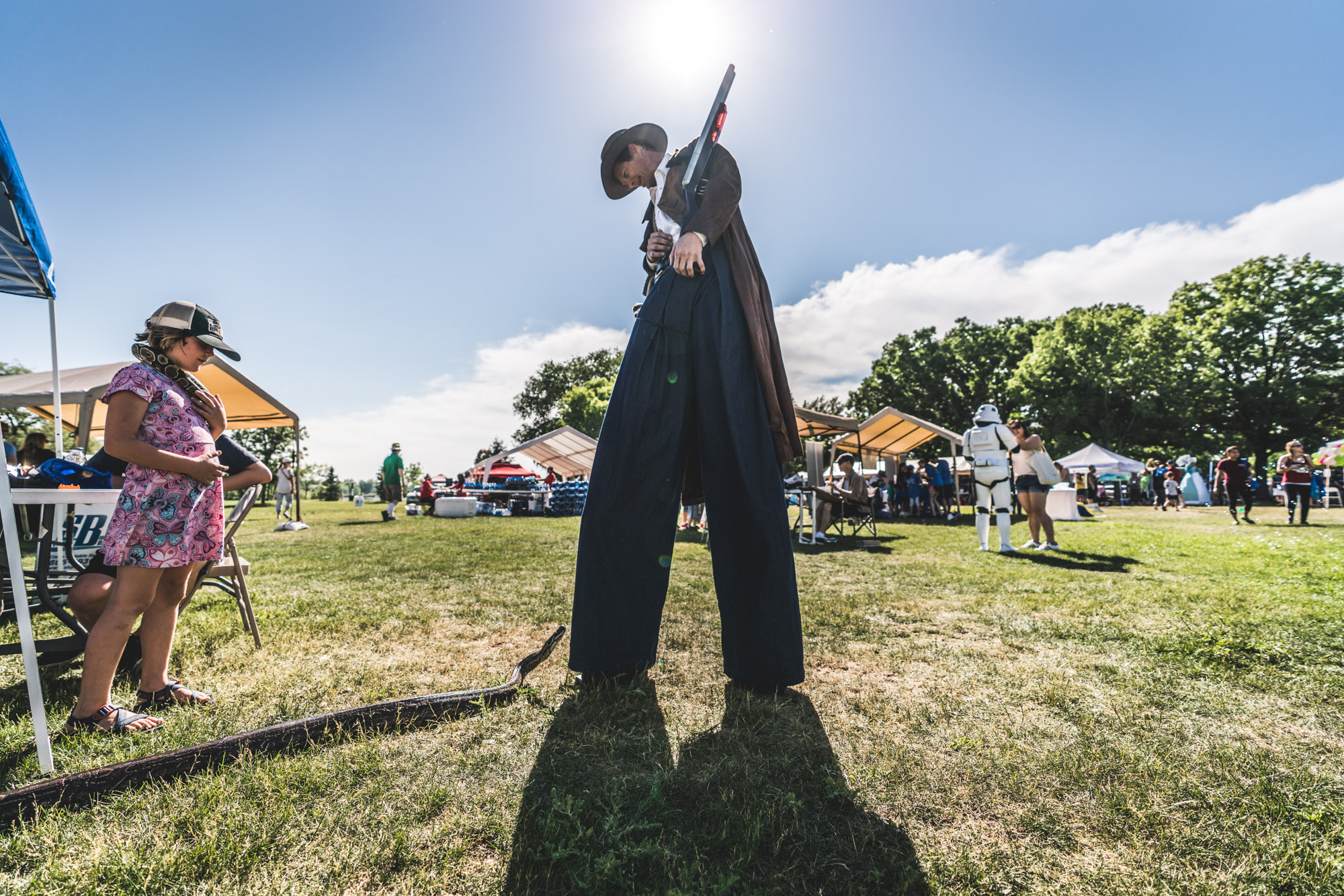 Man on stilts at an event ground looks down at a giant snake who is roaming free at the event