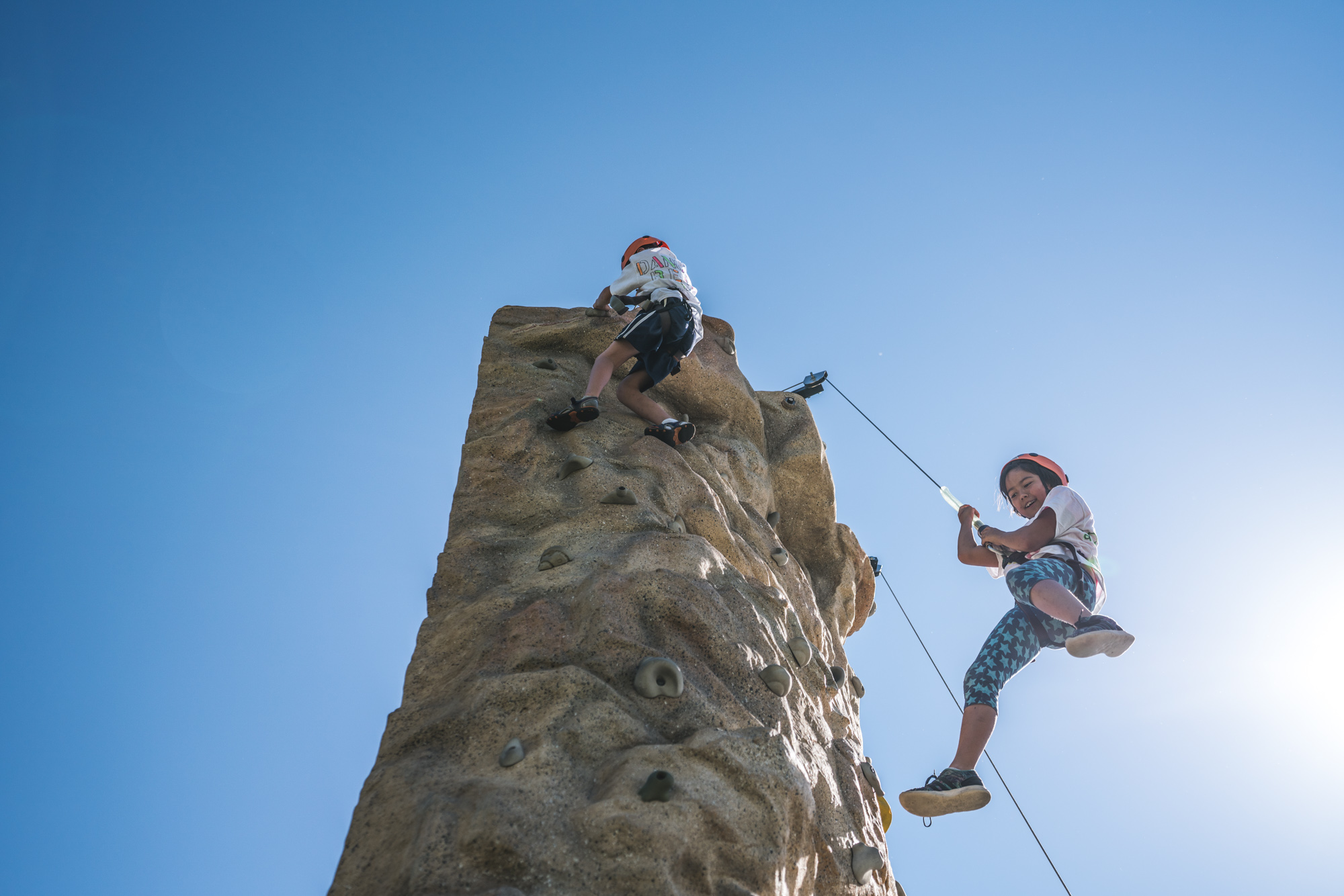Photo of two children at the top of a rock climbing wall, with the little girl repelling down