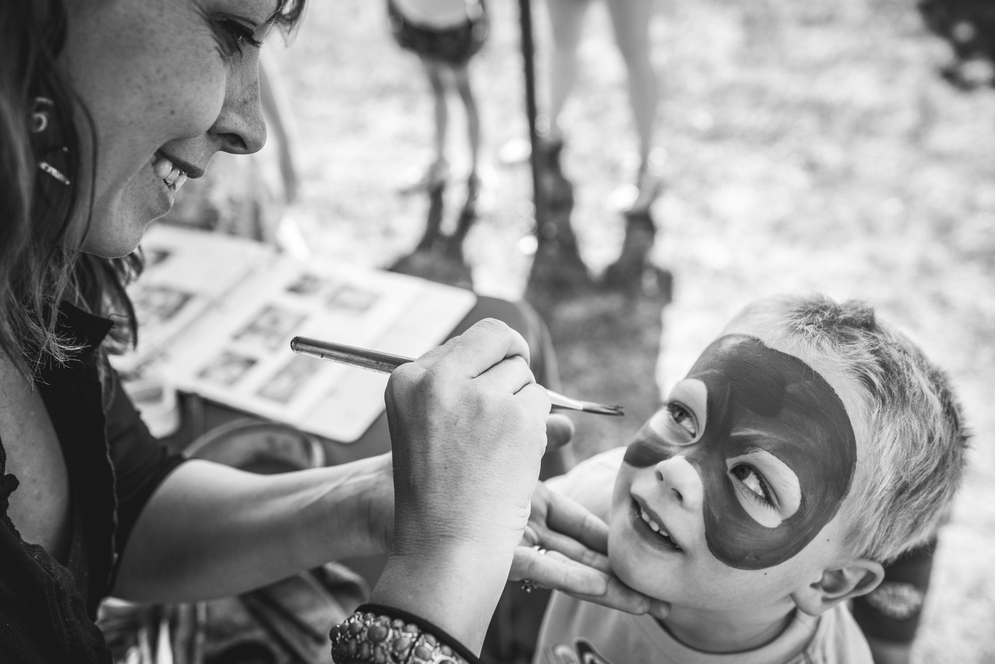 Black and white photograph of a little boy getting his face painted at an outside fundraising event in Denver, Colorado