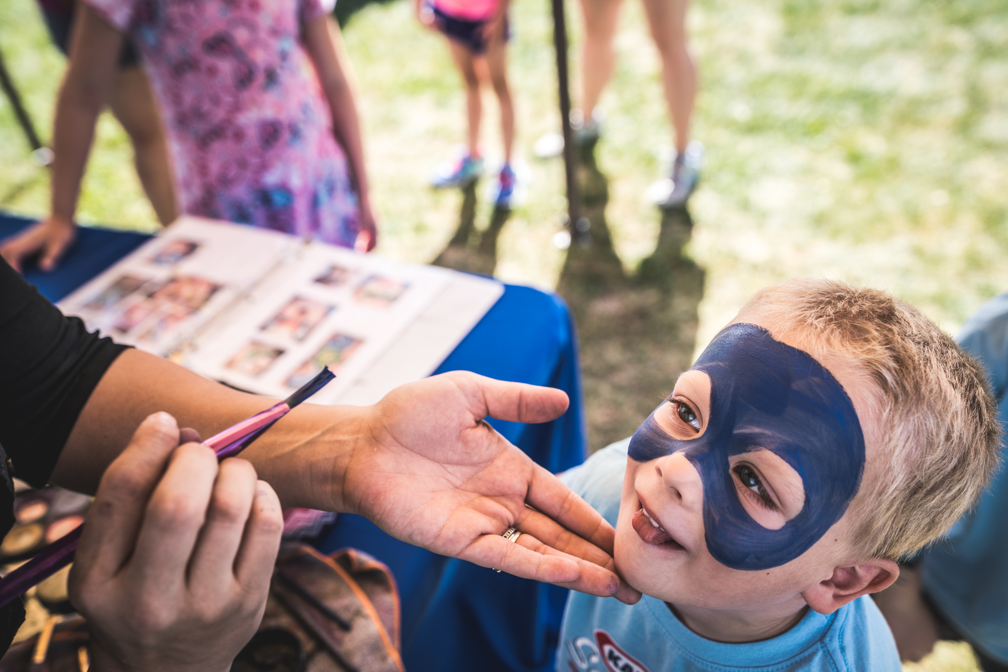 Color photo of a little boy getting his face painted blue at a charity event in Denver, Colorado