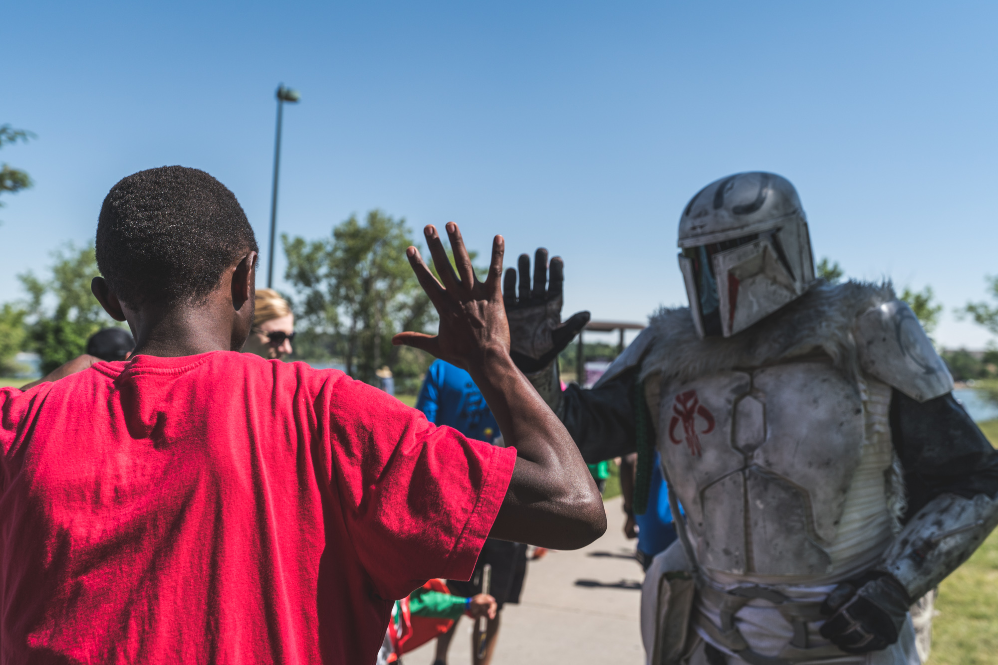 A kid high fives some kind of helmeted character at the ASC Walk With Autism event in Denver, CO.
