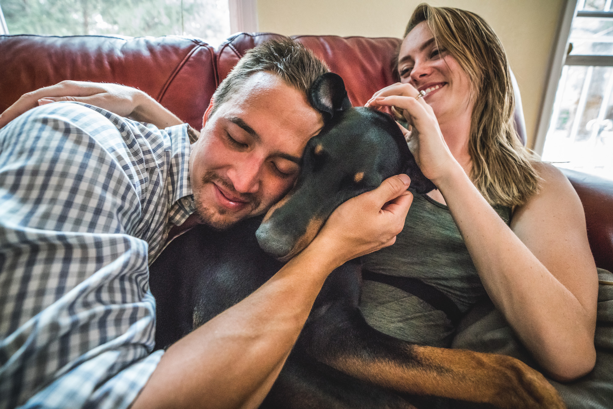 Man and woman on a red couch cuddle up with their doberman pincher