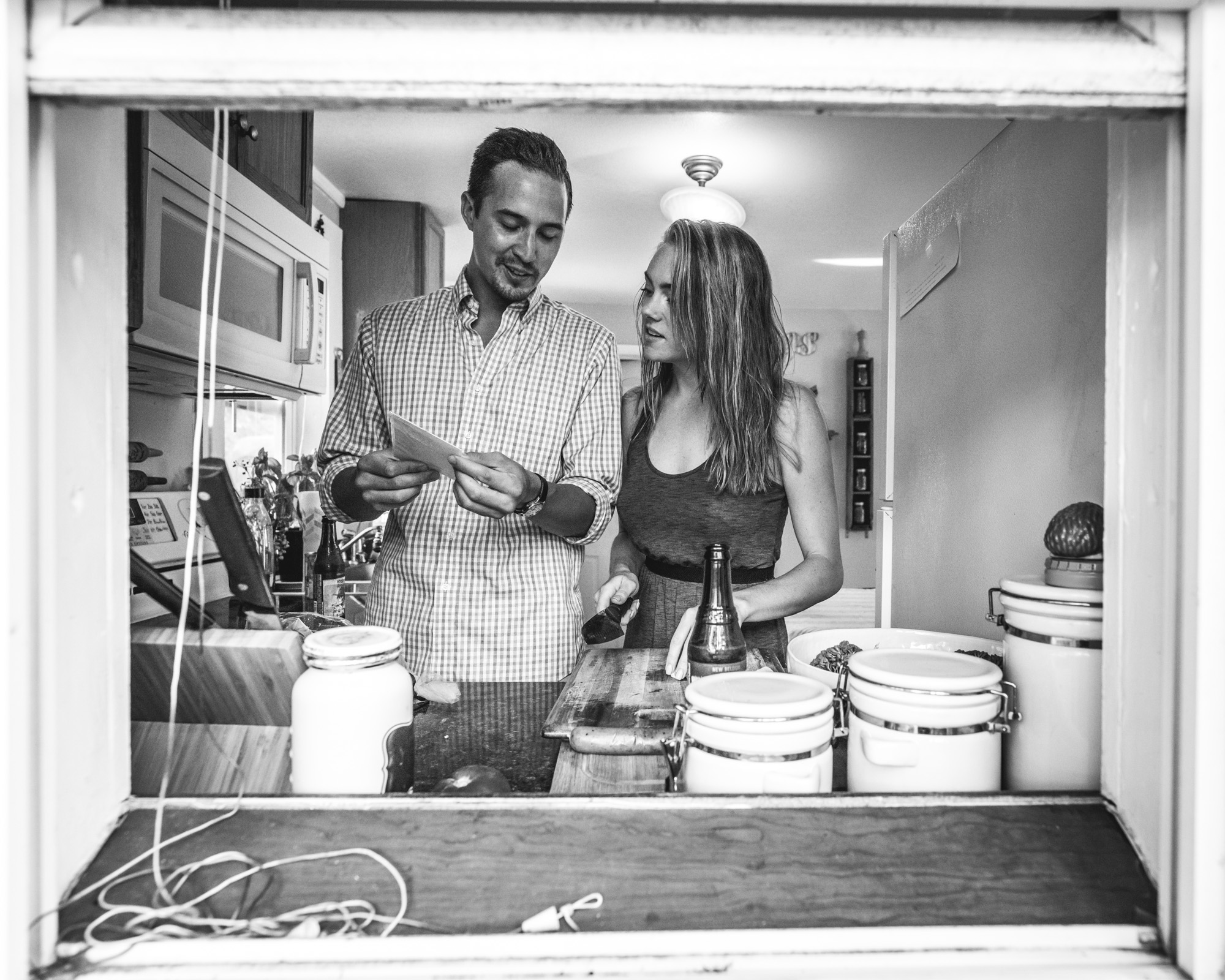 Black and white engagement photo looking in a window at a man and woman looking at a recipe together
