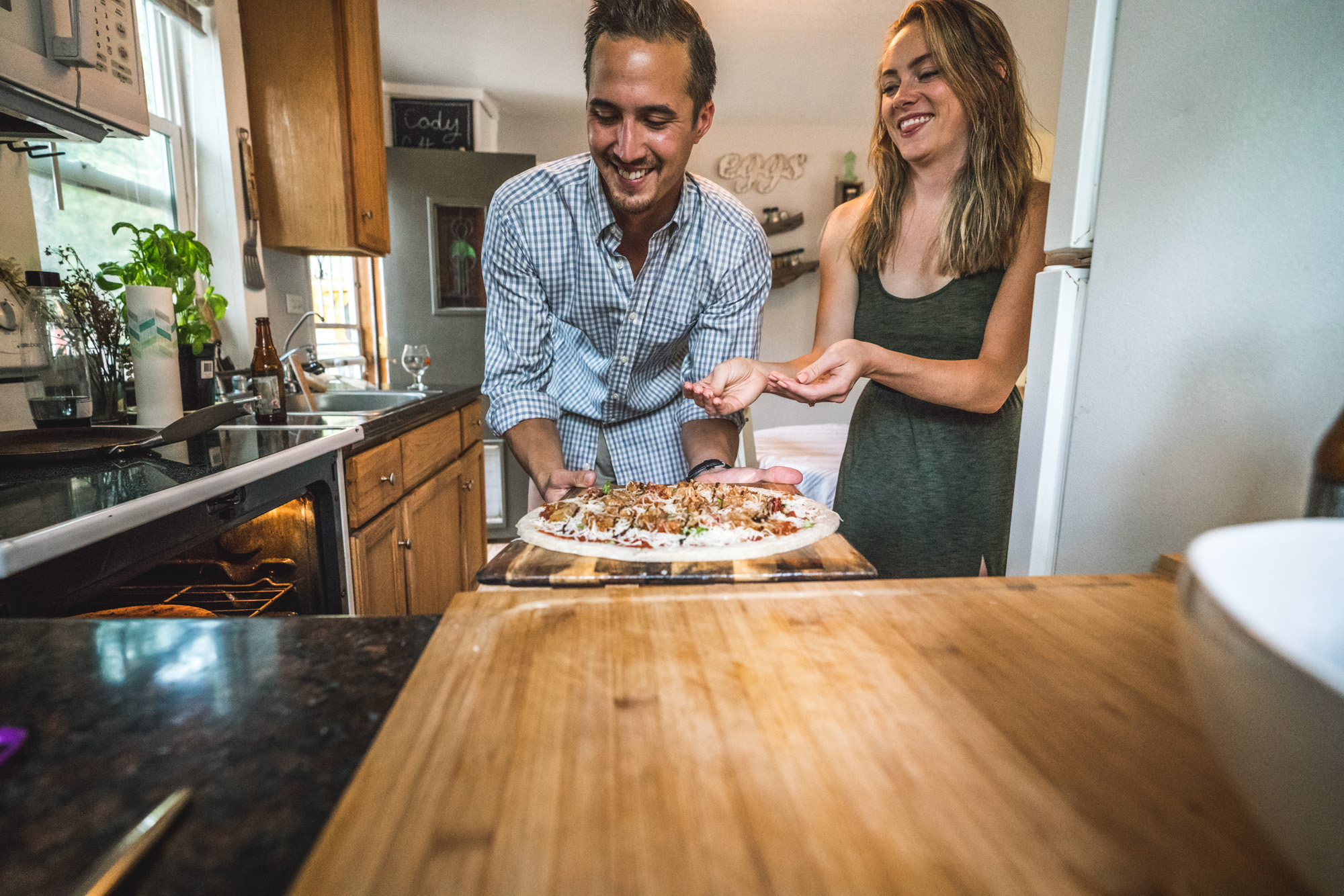 Engagement photo of a man and woman in their kitchen getting ready to put a pizza in the oven
