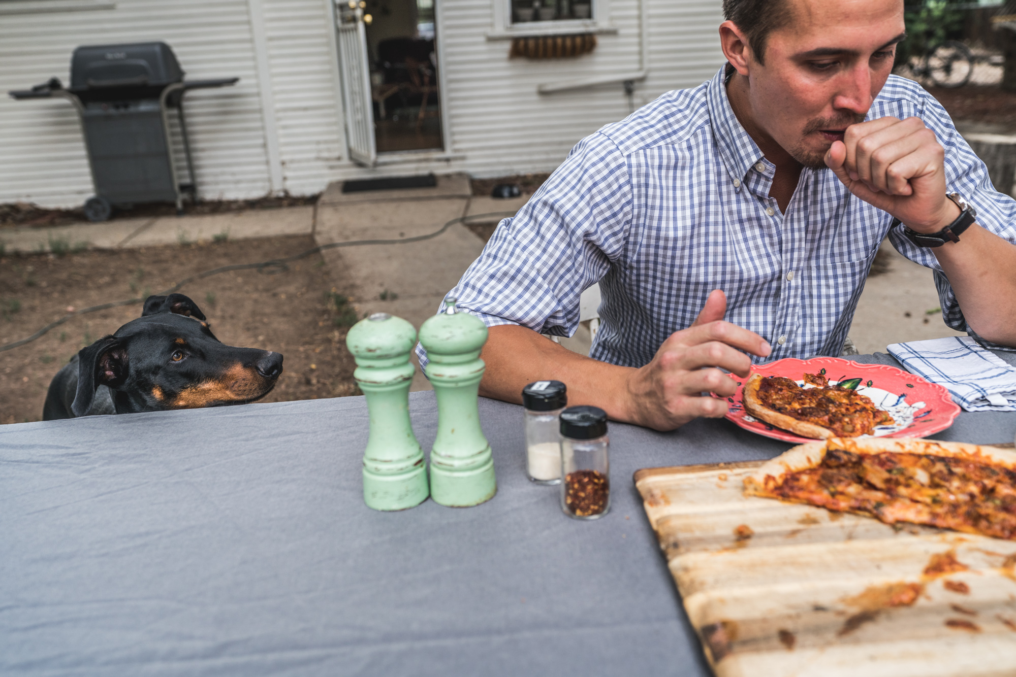 Man sitting at an outside table coughs after eating spicy pizza as his dog watches on
