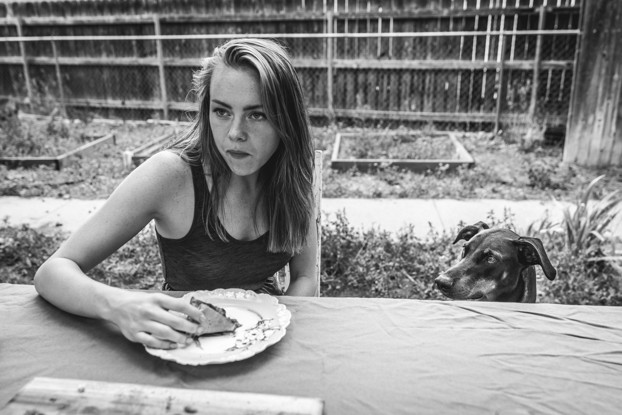 Black and white photo of a woman eating pizza at an outside table as her doberman pincher looks at the pizza longingly
