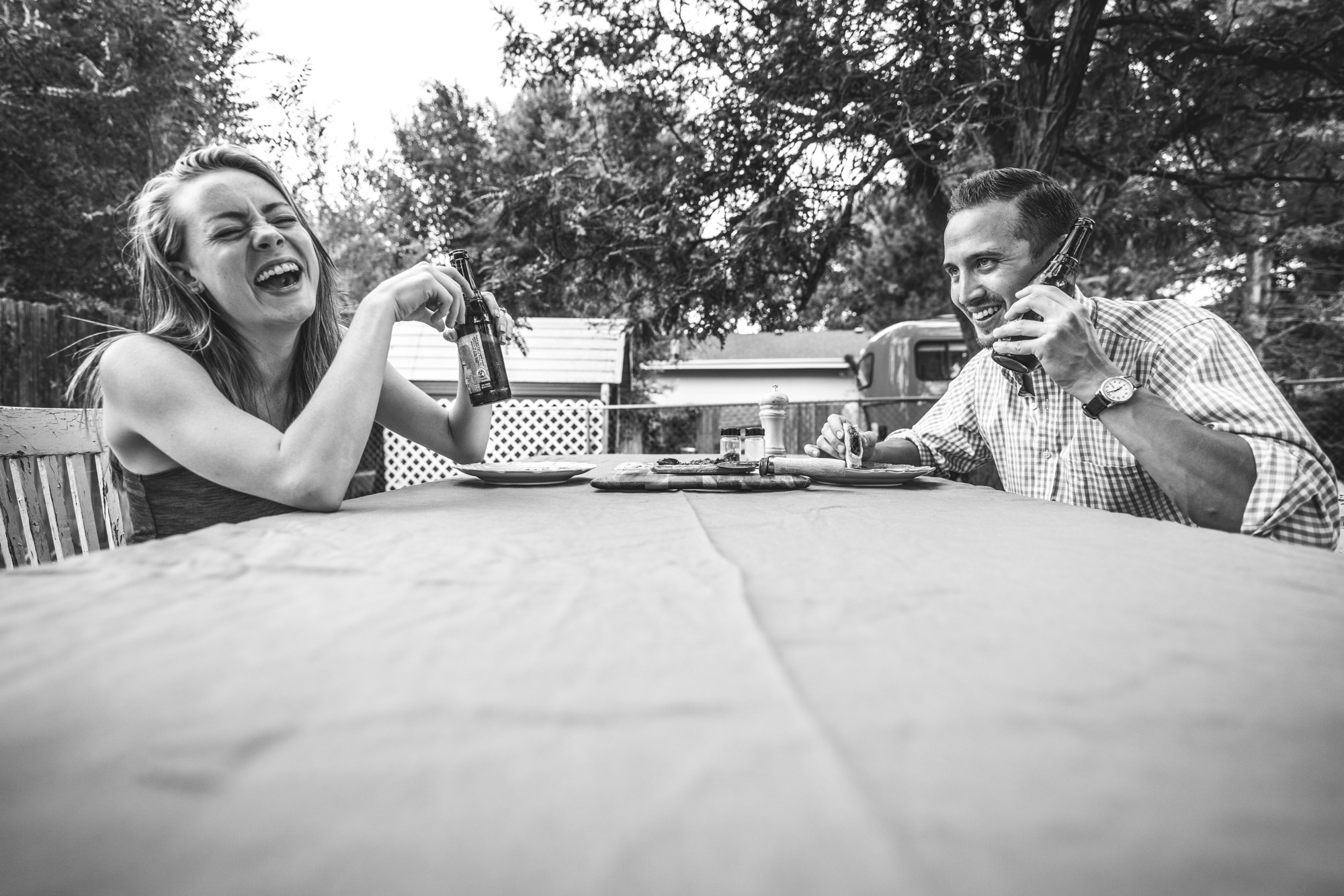Man and woman at an outside table laughing