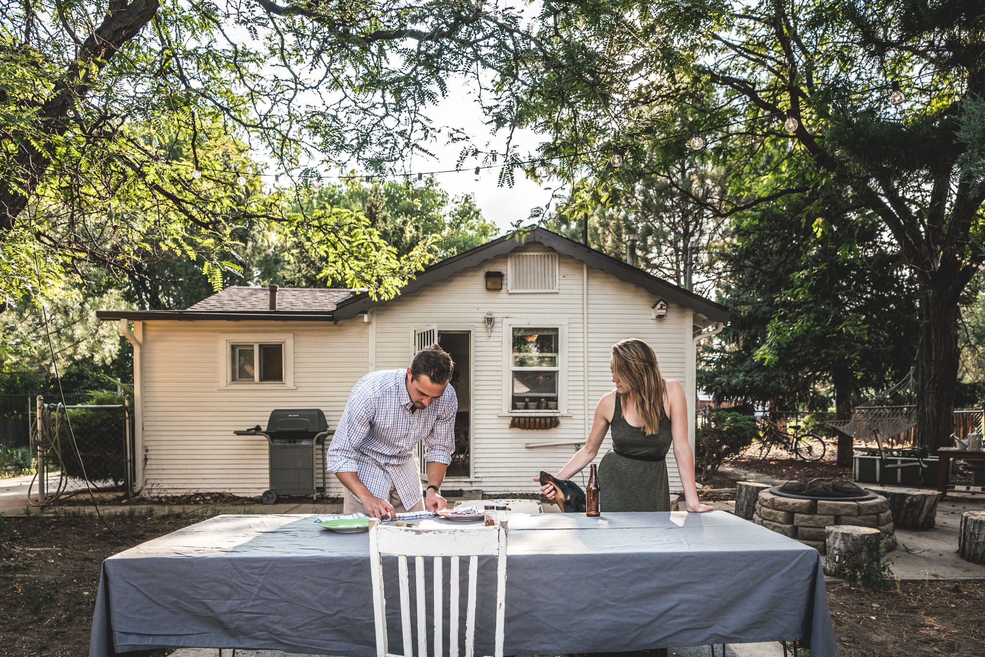 Man and woman at an outside table, the man setting the table and the woman petting their dog