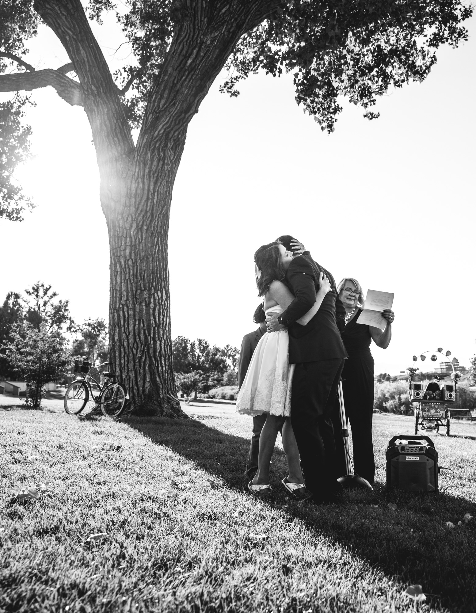 Black and white photo of a bride and groom hugging under a giant tree in Berkeley Park in Denver, Colorado