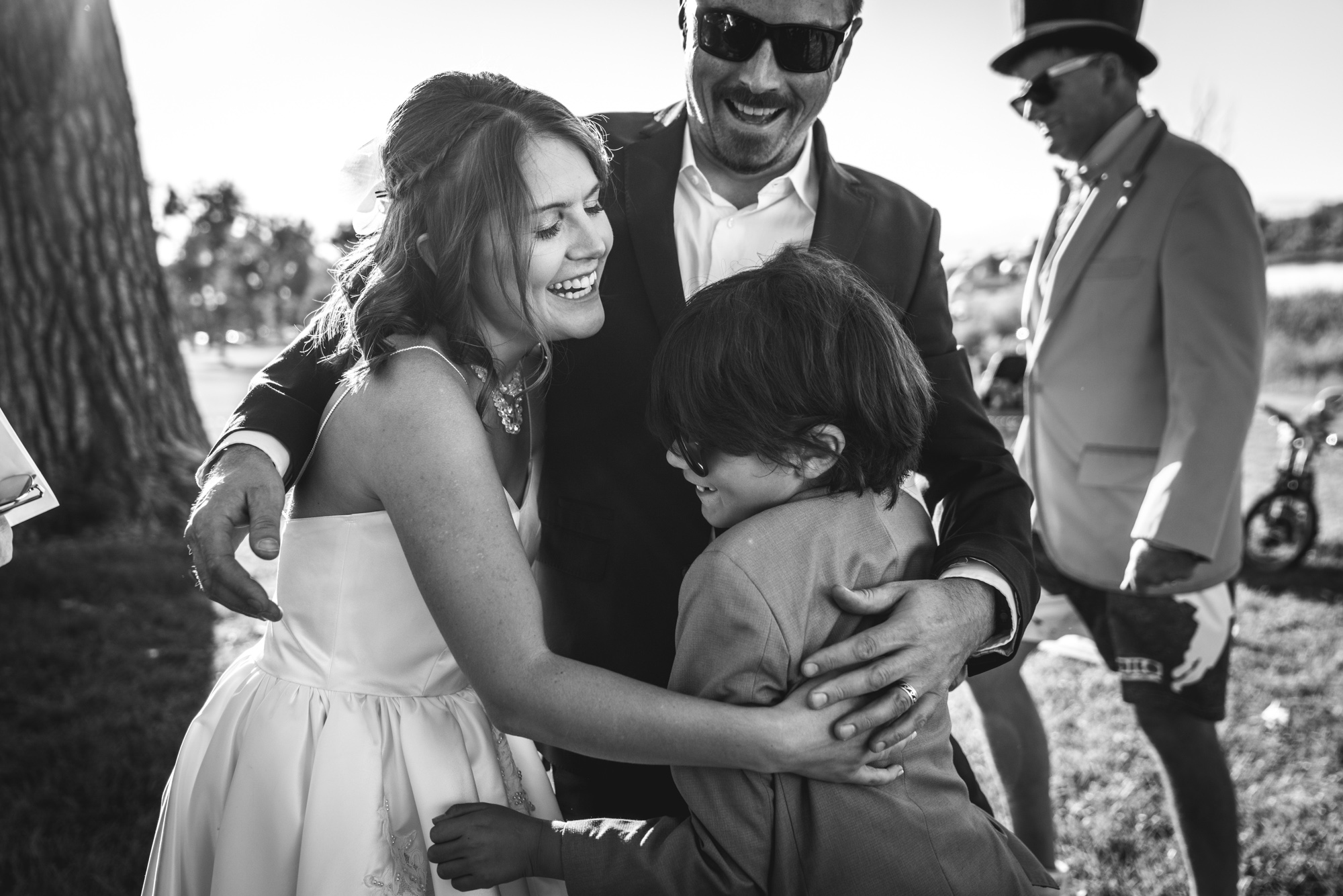 Bride, groom, and groom's young son give each other a big hug and smile in celebration of bride and groom getting married