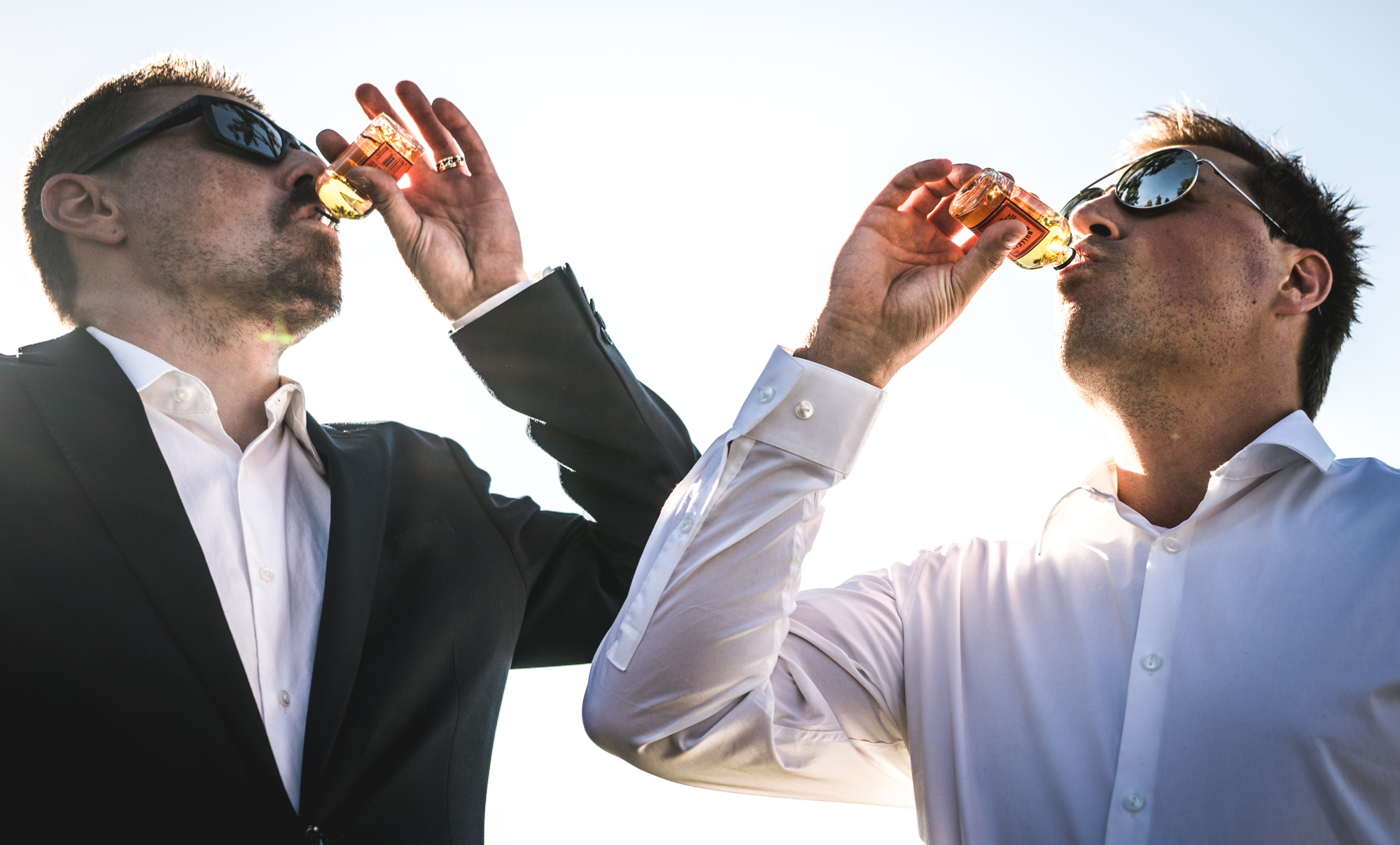Groom and guest at a wedding take shots of Fireball