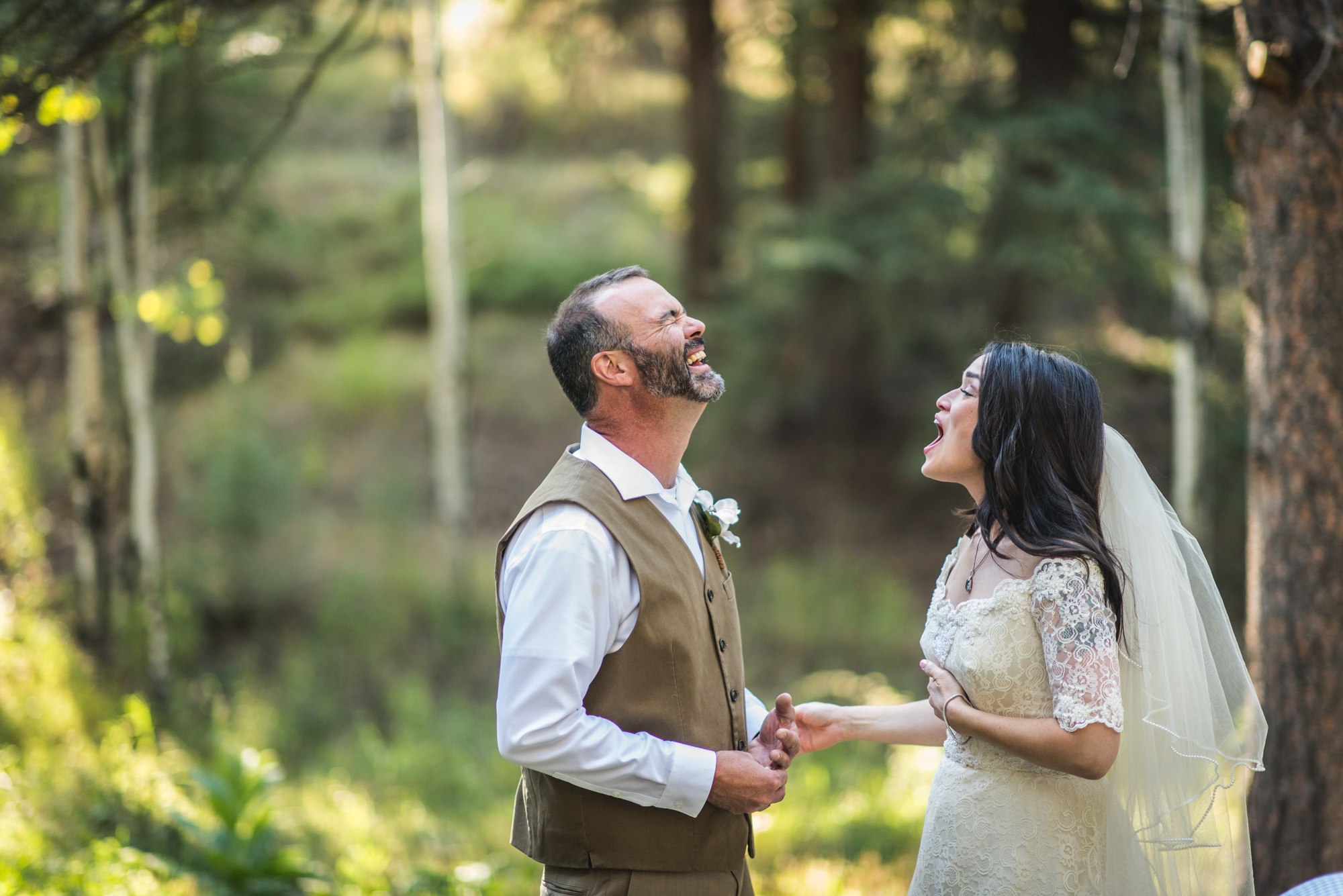 Bride and groom laugh together in the woods at their wedding