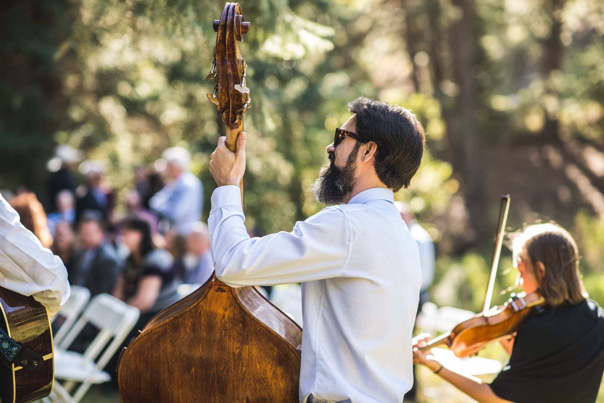 Man plays a cello and woman plays the violin at a wedding ceremony in the woods of Morrison, Colorado