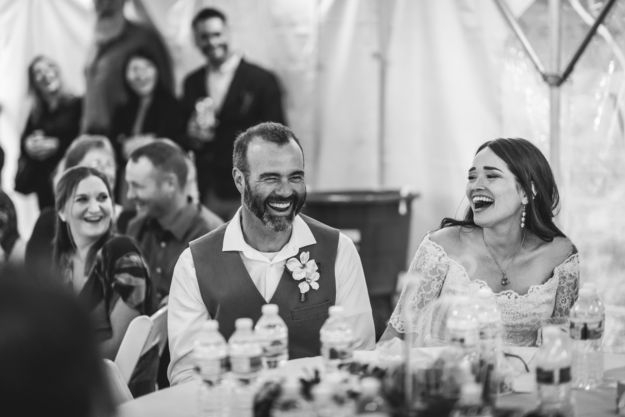 Documentary photo of a bride and groom laugh together at their wedding reception