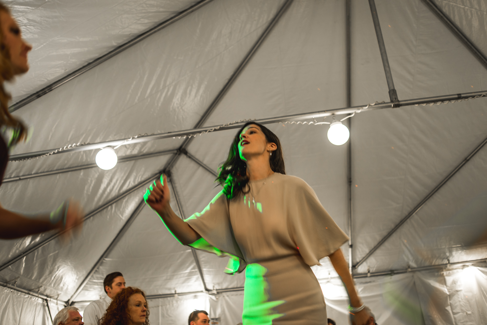Woman dances in bright green lights at a wedding reception