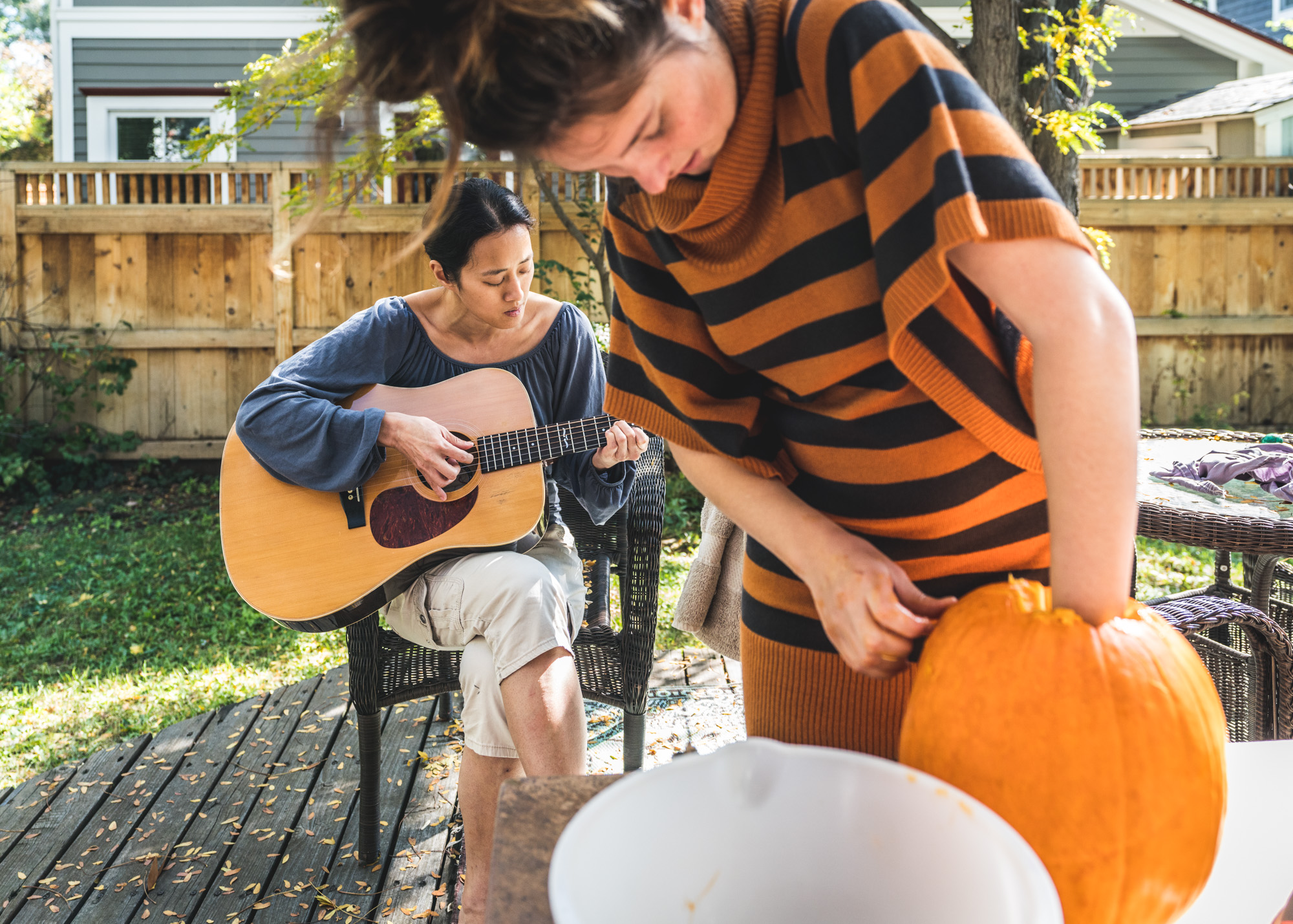Young woman carves a pumpkin as another woman plays guitar behind her