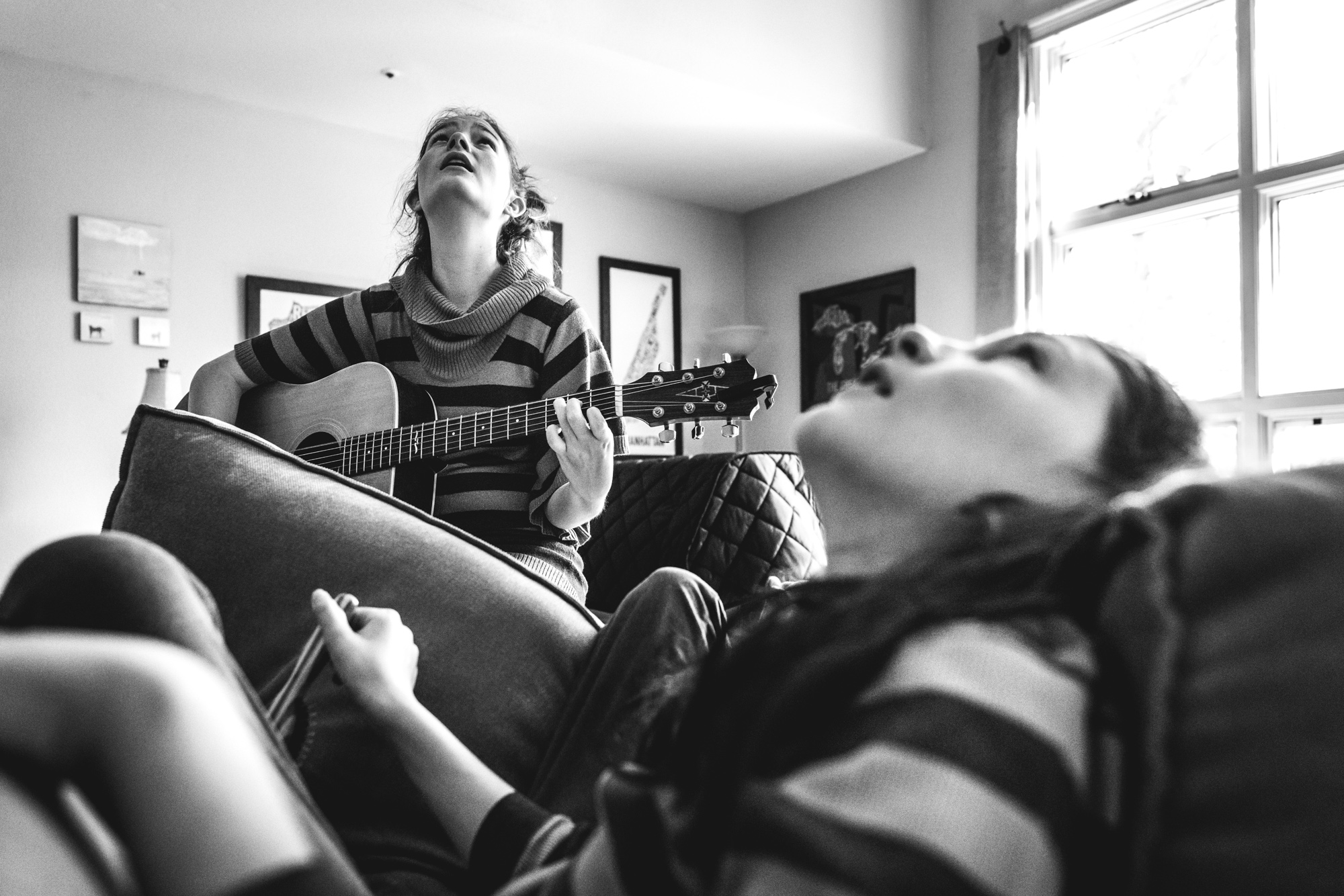 Two children sitting on a couch, one with a guitar, look up