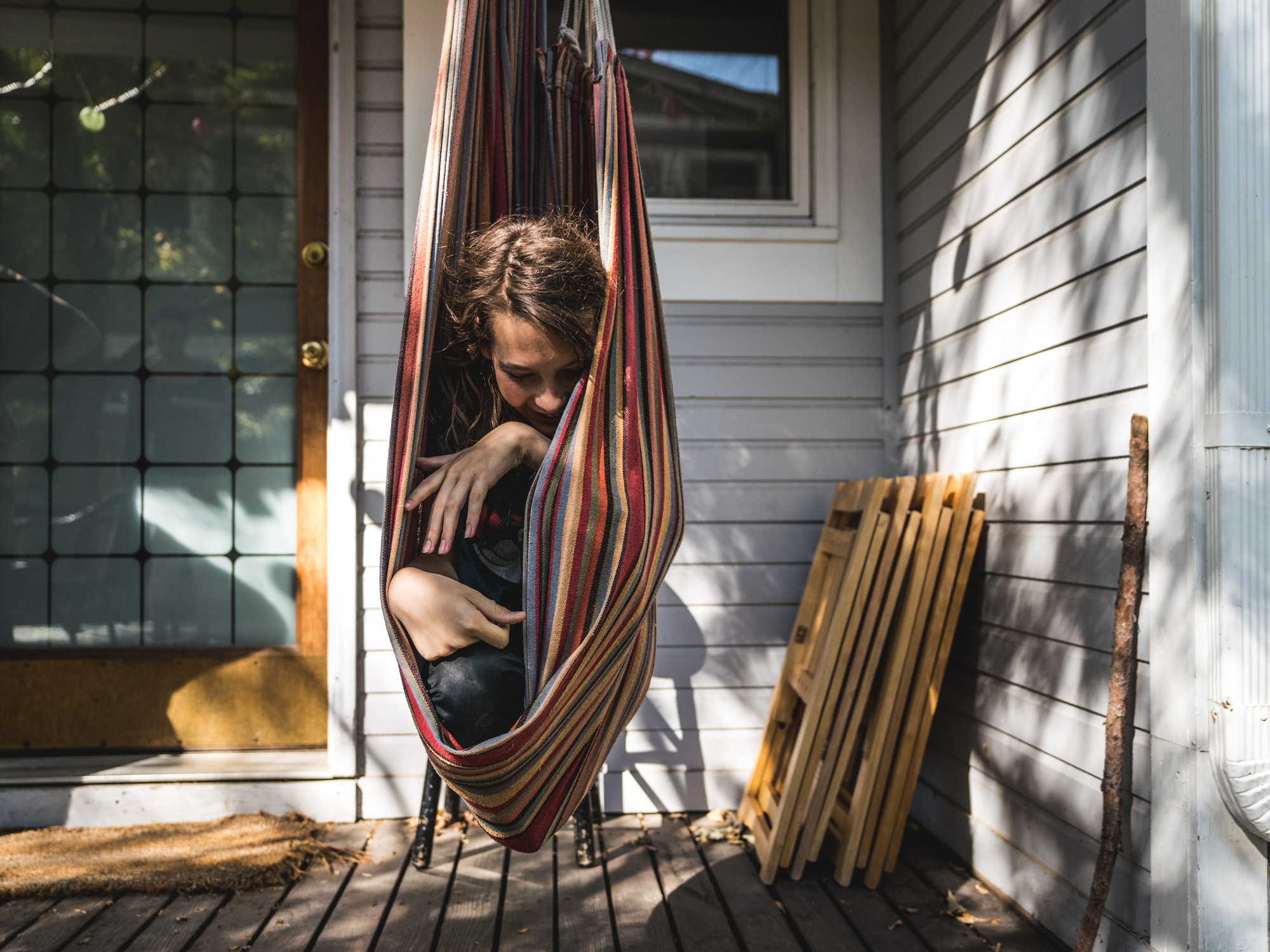 Young boy hangs in a porch swing