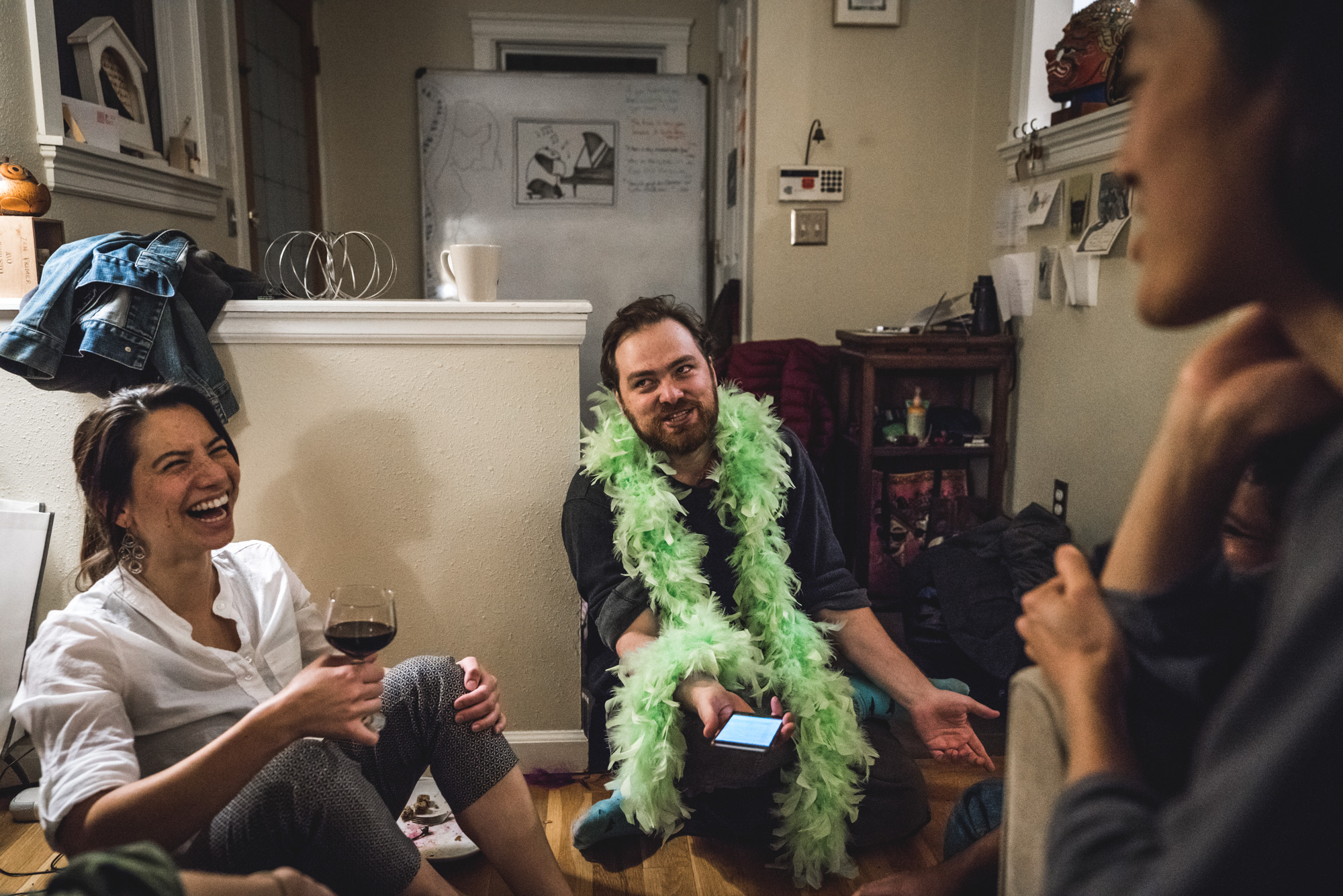 Man wearing a green boa sits on the floor and laughs and drinks wine with friends
