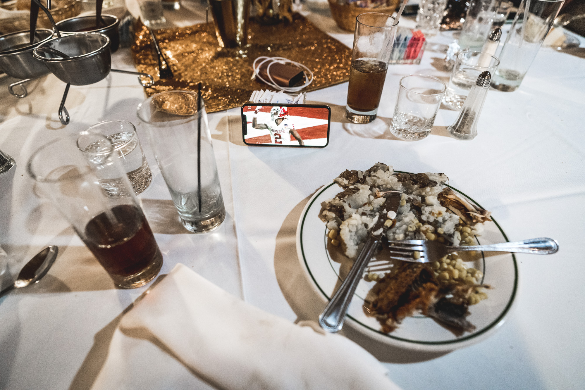 Photo of a table with food on it and a phone propped up with a football game playing on the screen