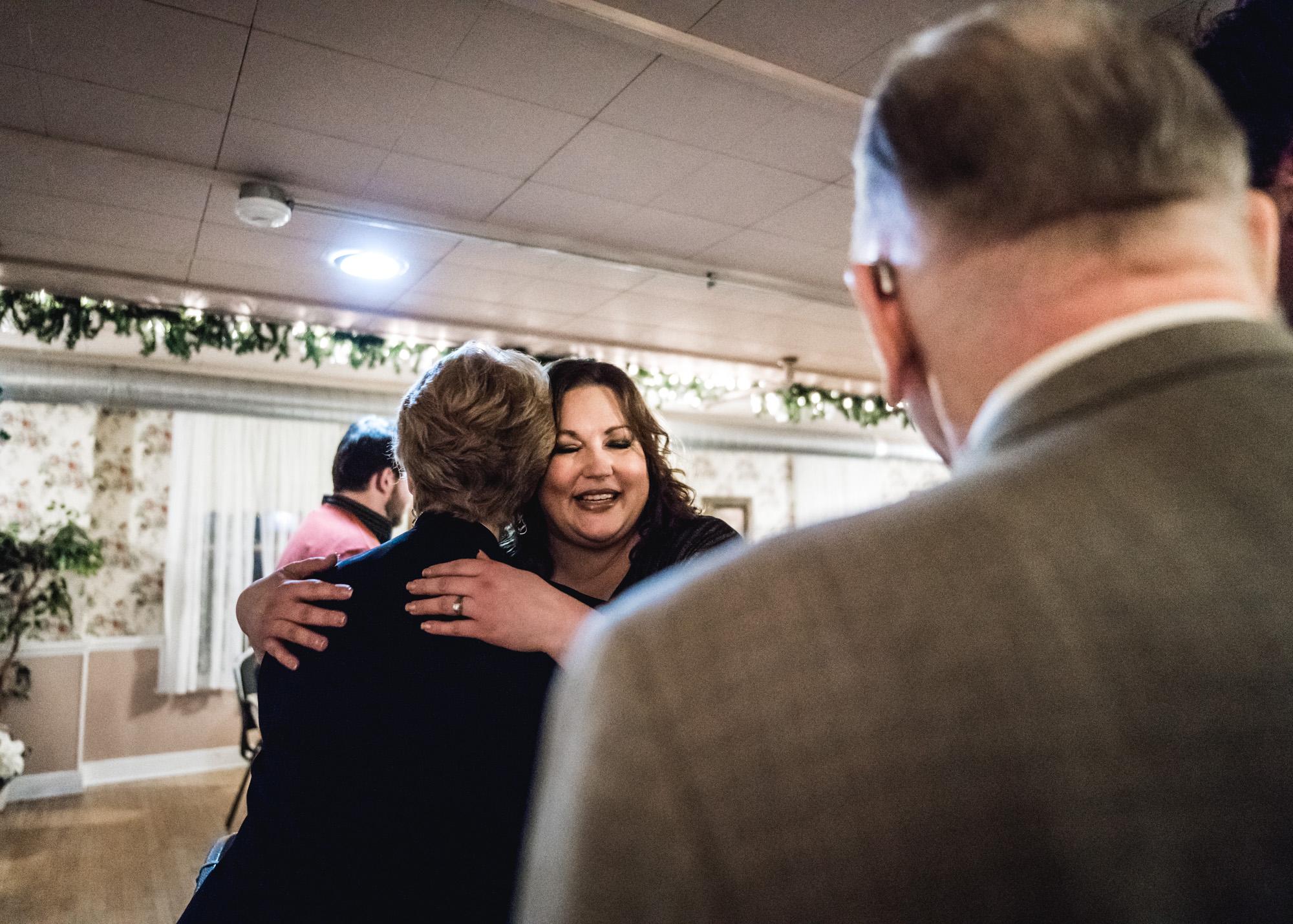 Bride smiles as she hugs a wedding guest