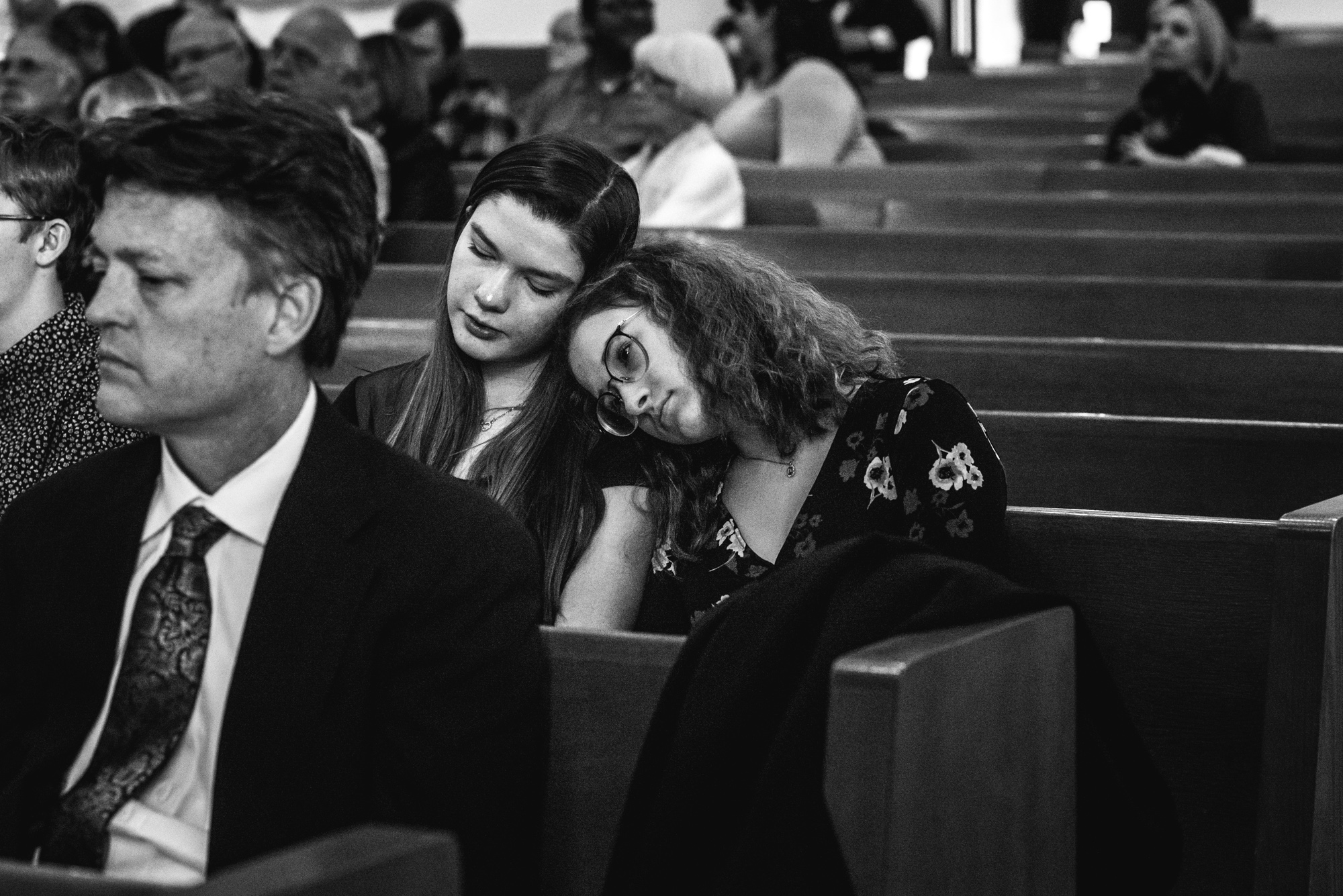 A girl rests her head on her sister's shoulder as they cry in grief during their grandmother's funeral at Greeley United Methodist Church in Greeley, Colorado