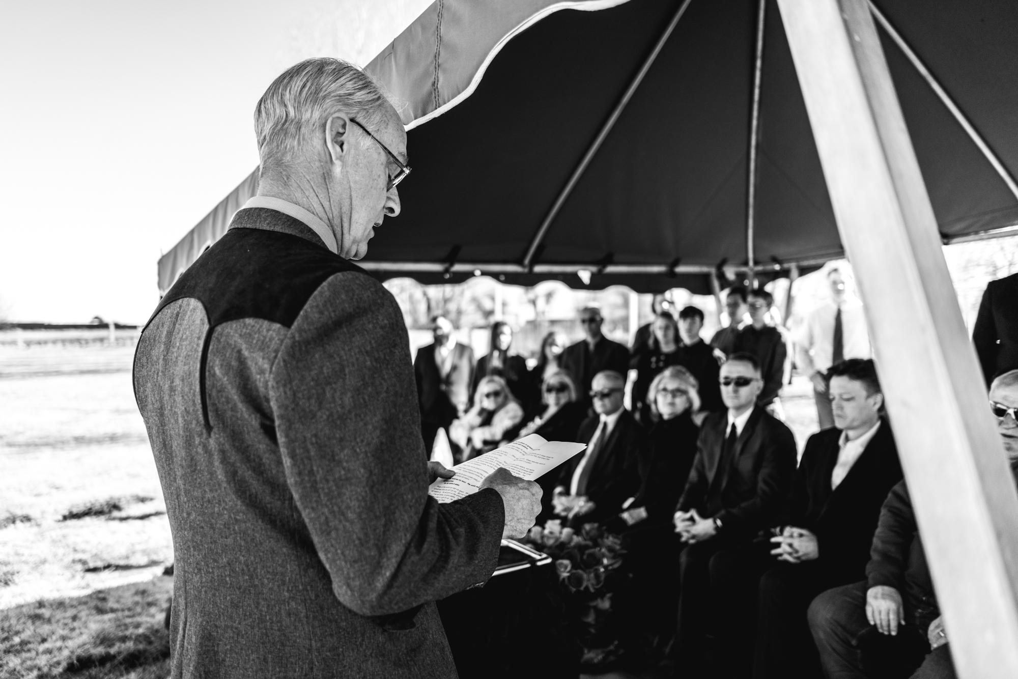 A man gives a eulogy under a tent during a memorial service in a cemetery in Greeley, Colorado