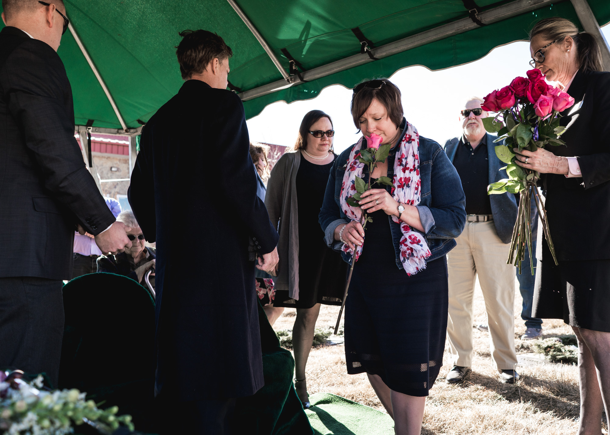 A woman smells a rose as she prepares to place it on the final resting place of her beloved grandmother during her memorial service at a cemetery in Greeley, CO