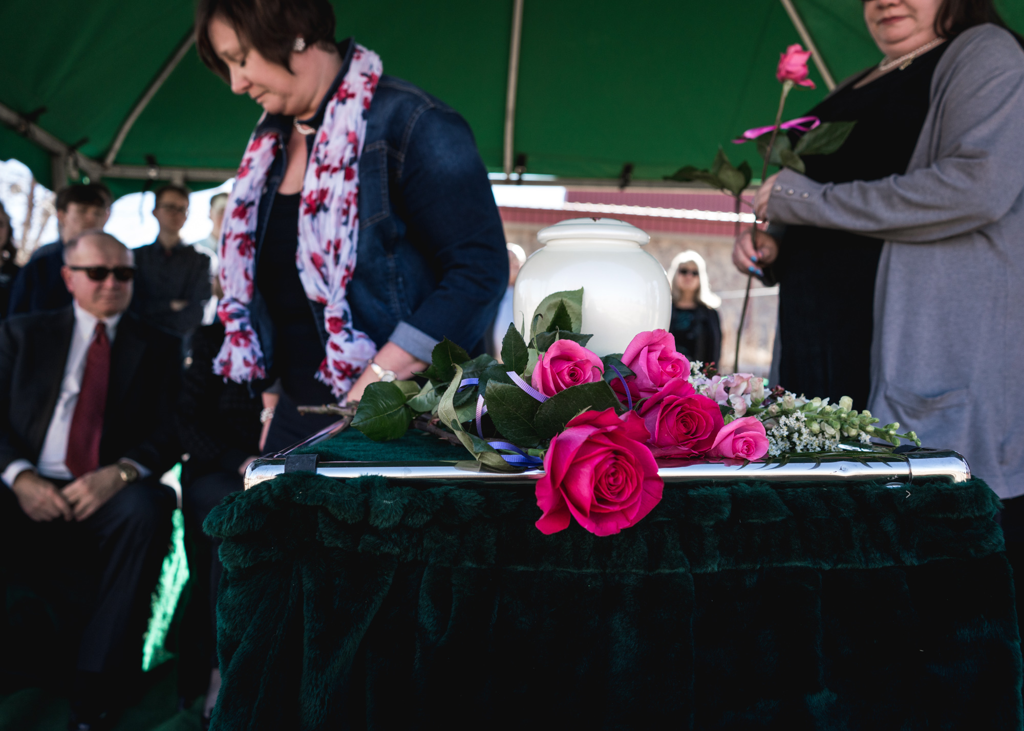 Family members place roses on the final resting place of their beloved family member during her memorial service at a cemetery in Greeley, Colorado