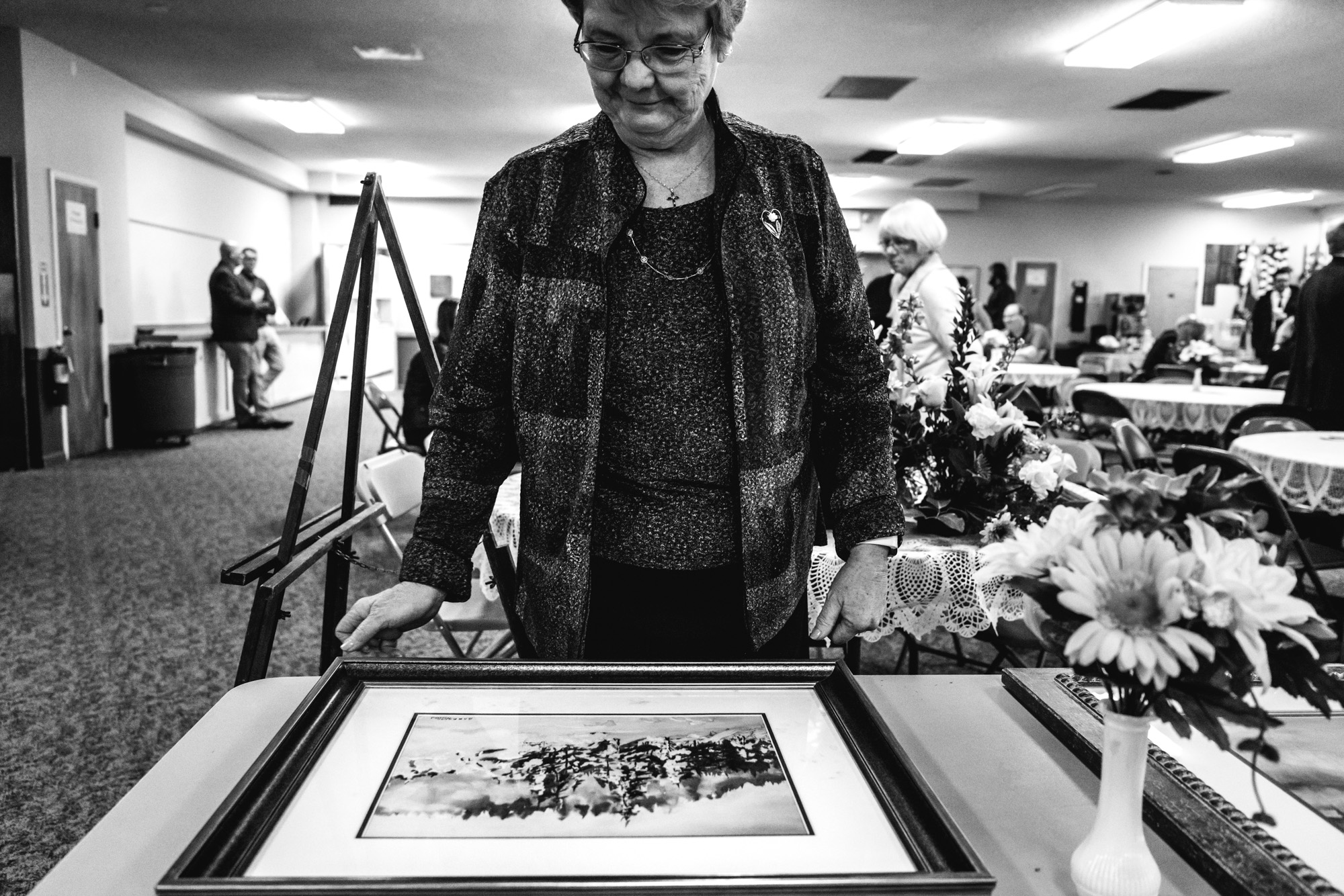 A woman looks at the artwork of Barbara Richard, whose memorial service she was attending