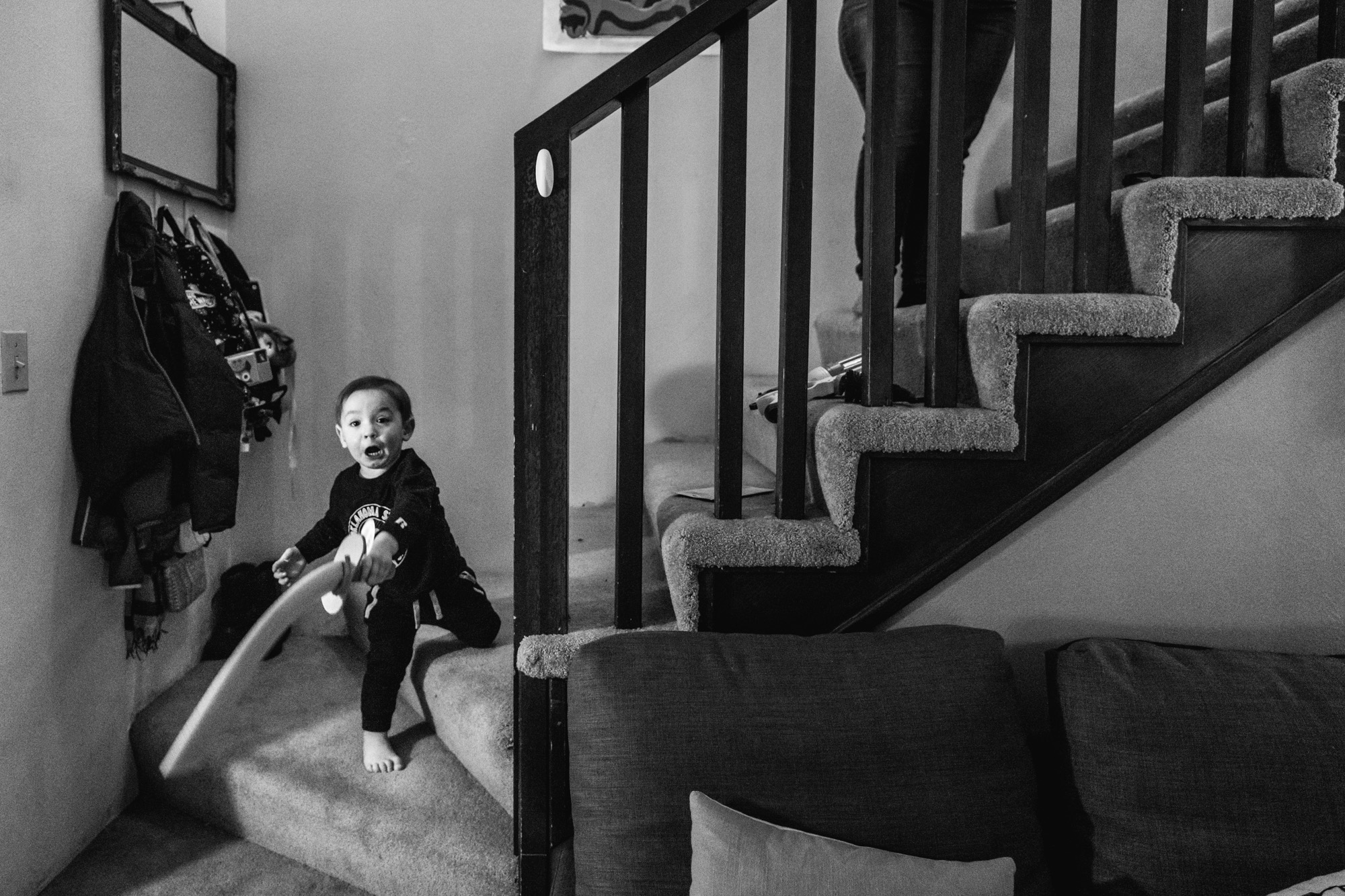 Little boy standing on his stairs at home swings a sword at the camera