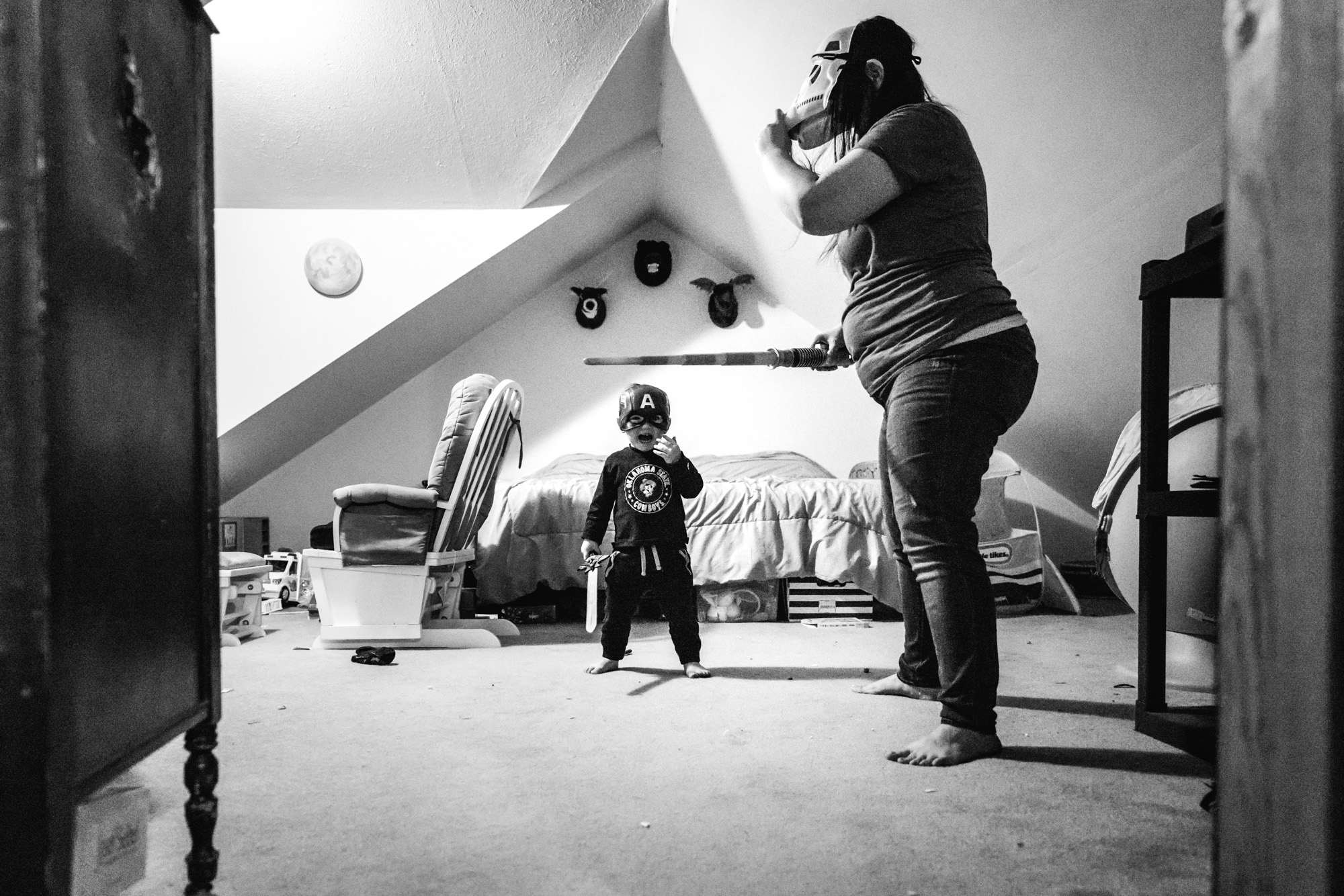 Mother and son both wear a mask and sword in mom's bedroom
